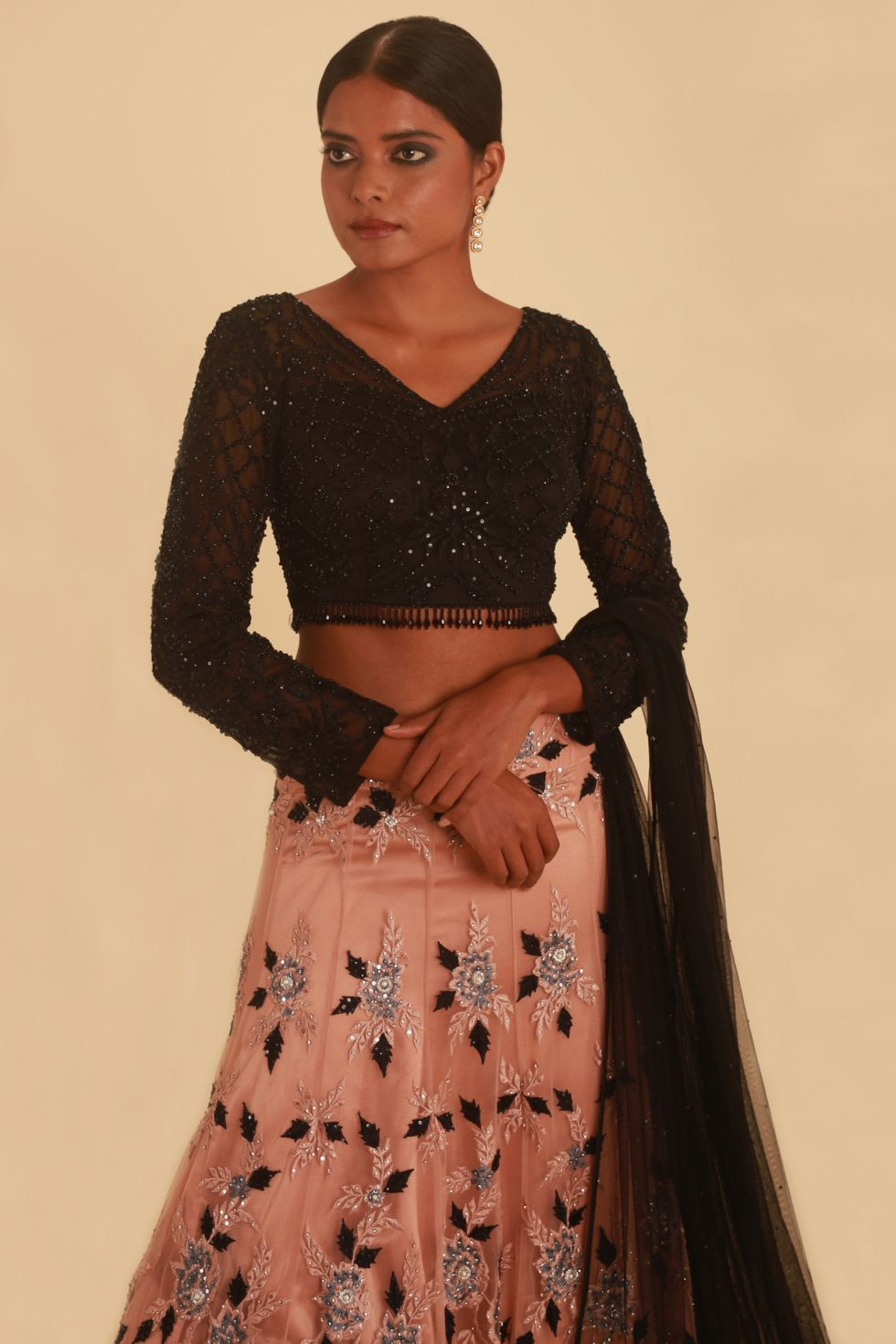 Nude pink lehenga with floral details and contrast black tasseled choli