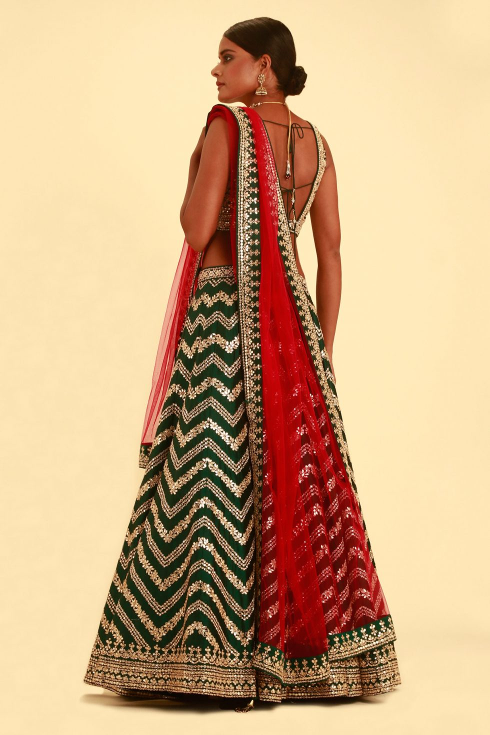 Moss green gota work lehenga set with a contrast red dupatta and gold embellishments