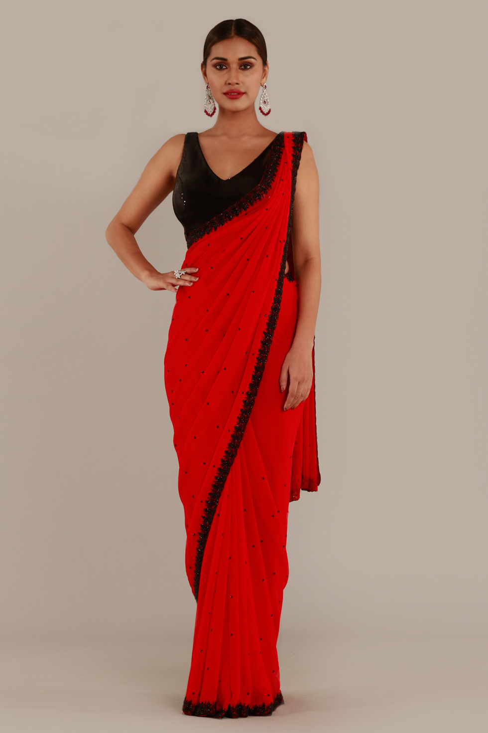 Bright red classic saree with black border and stone work and contrast black sequinned choli with tie up back