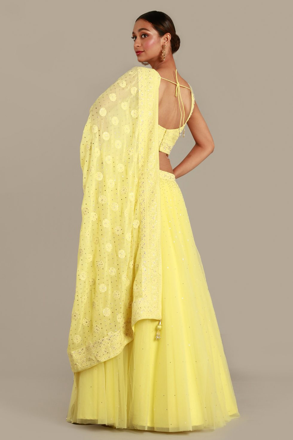 Sunshine yellow tulle lehenga set with matching dupatta and choli with thread work and gold and silver embellishments