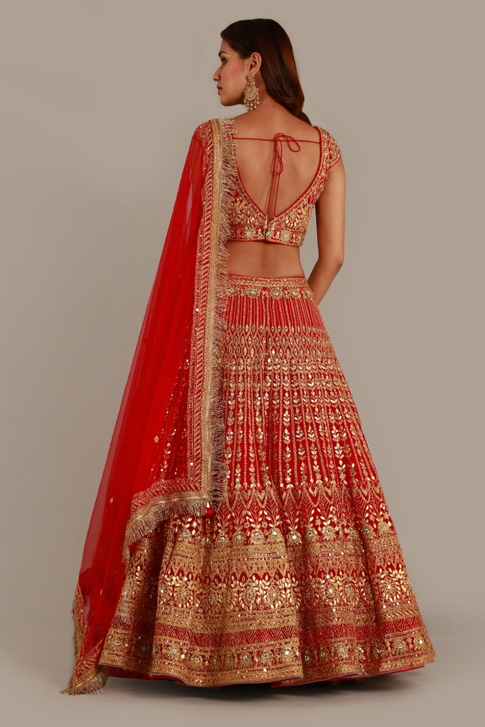 Bright red lehenga set with gota and abla work and matching dupatta with gold border and fringe detail
