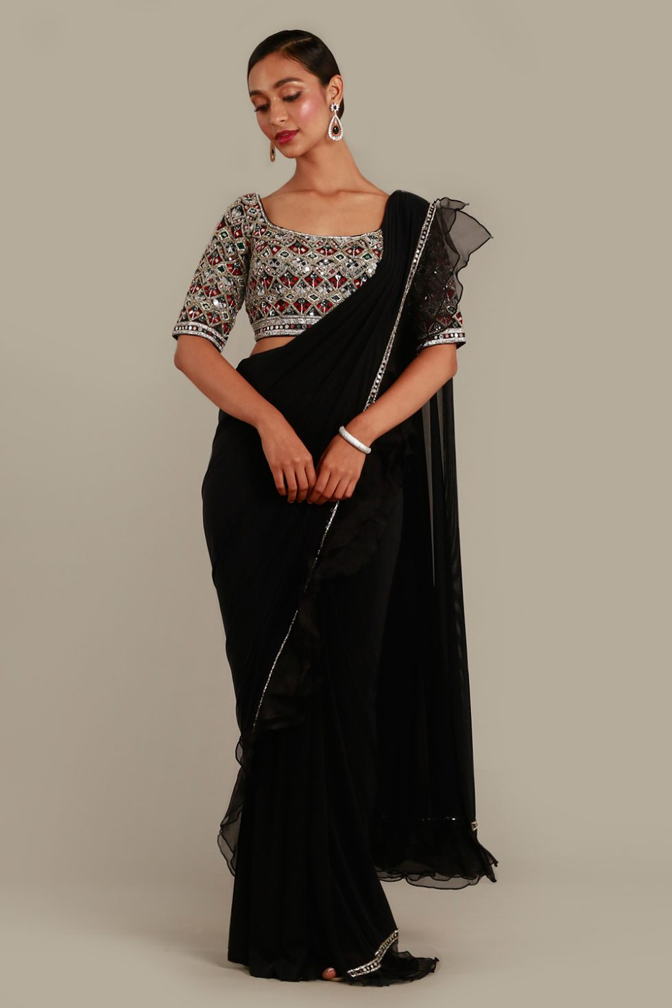 Jet black pre-stitched saree with ruffle details and matching choli with contrast thread work, mirror embroidery and silver embellishments.