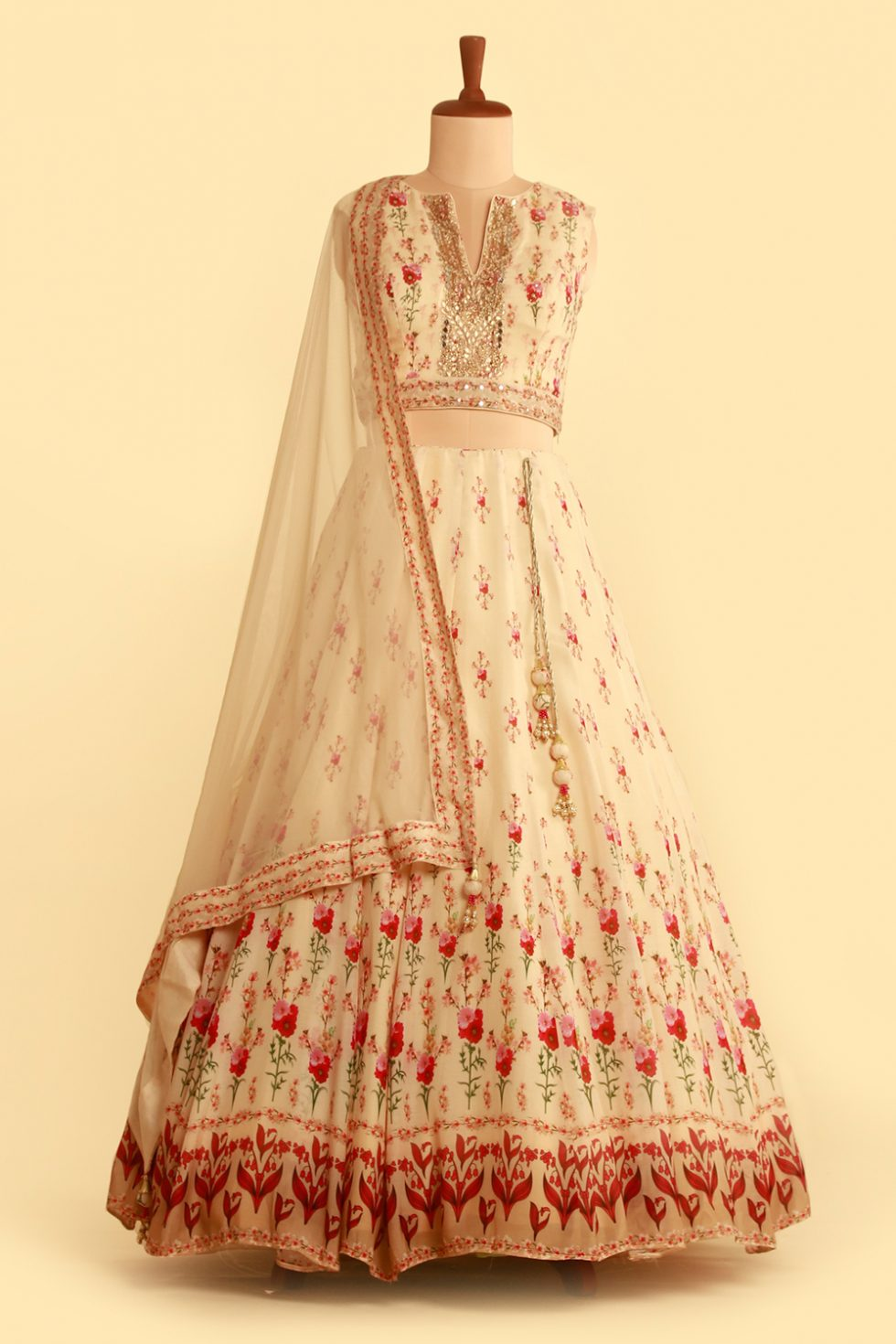 Cream printed lehenga set with matching dupatta and gold embellishments