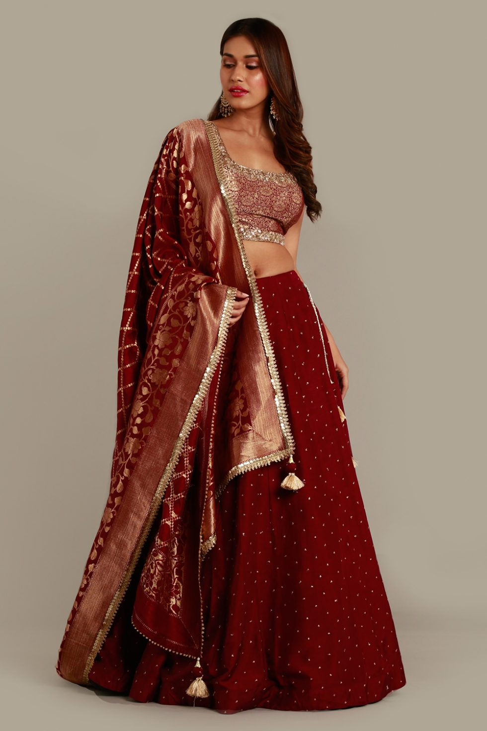 Deep red maroon lehenga set with gold butis, Banarasi dupatta and brocade blouse with gold embroidered neckline