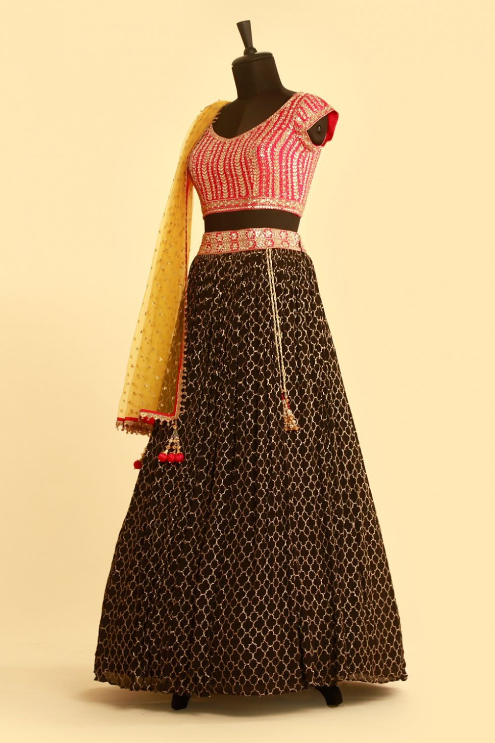 Deep black lehenga with contrast pink choli and contrast yellow dupatta with gold embellishments