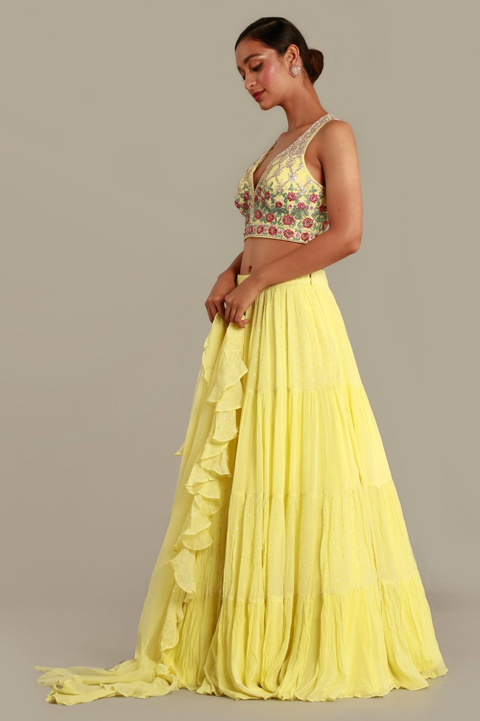 Lemon yellow lehenga set with tiered skirt, matching blouse with multi coloured embroidery, silver details and frill dupatta