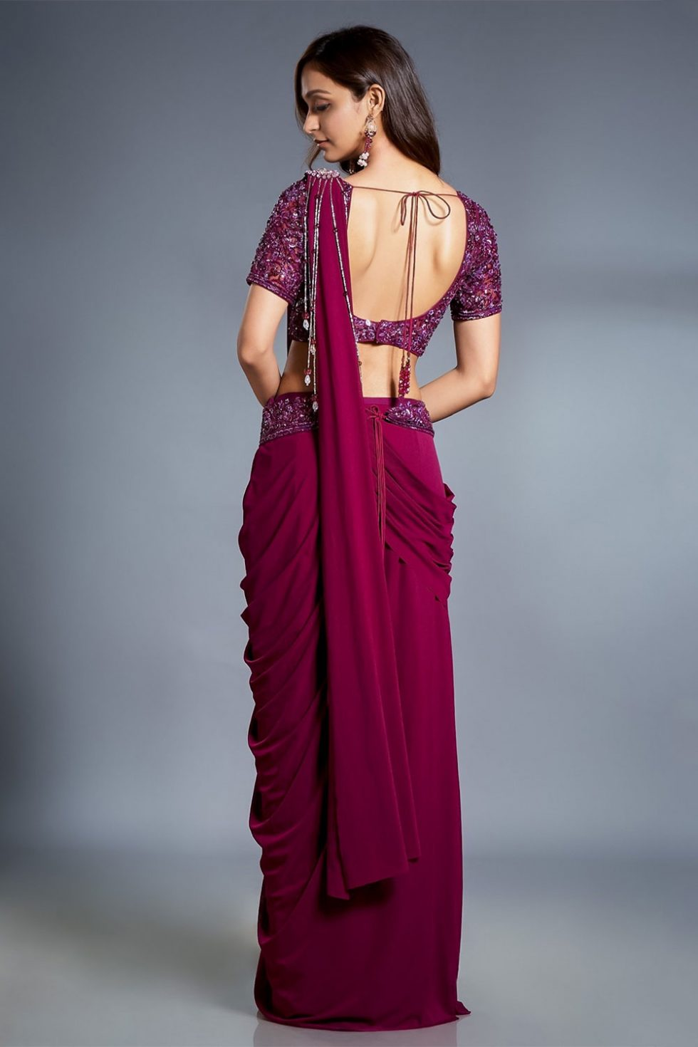 Magenta purple pre stitched draped saree and matching hand embroidered blouse with 'kamarbandh' and jewelled broach with tassels.