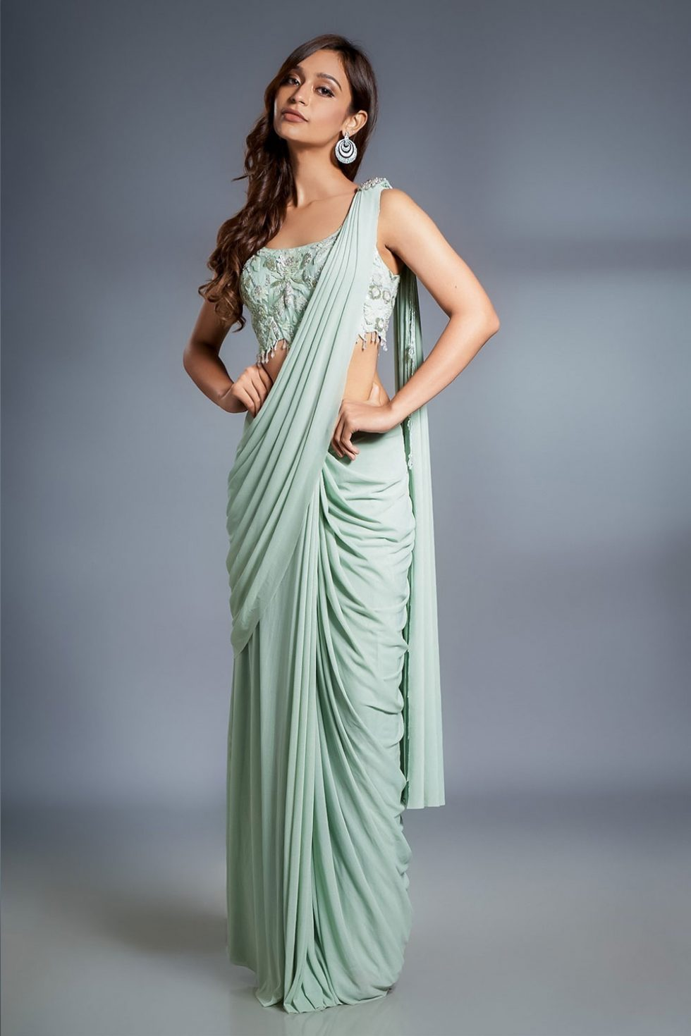 Mint green pre stitched draped saree and matching hand embroidered blouse with cut work and a jewelled broach with tasseled details.