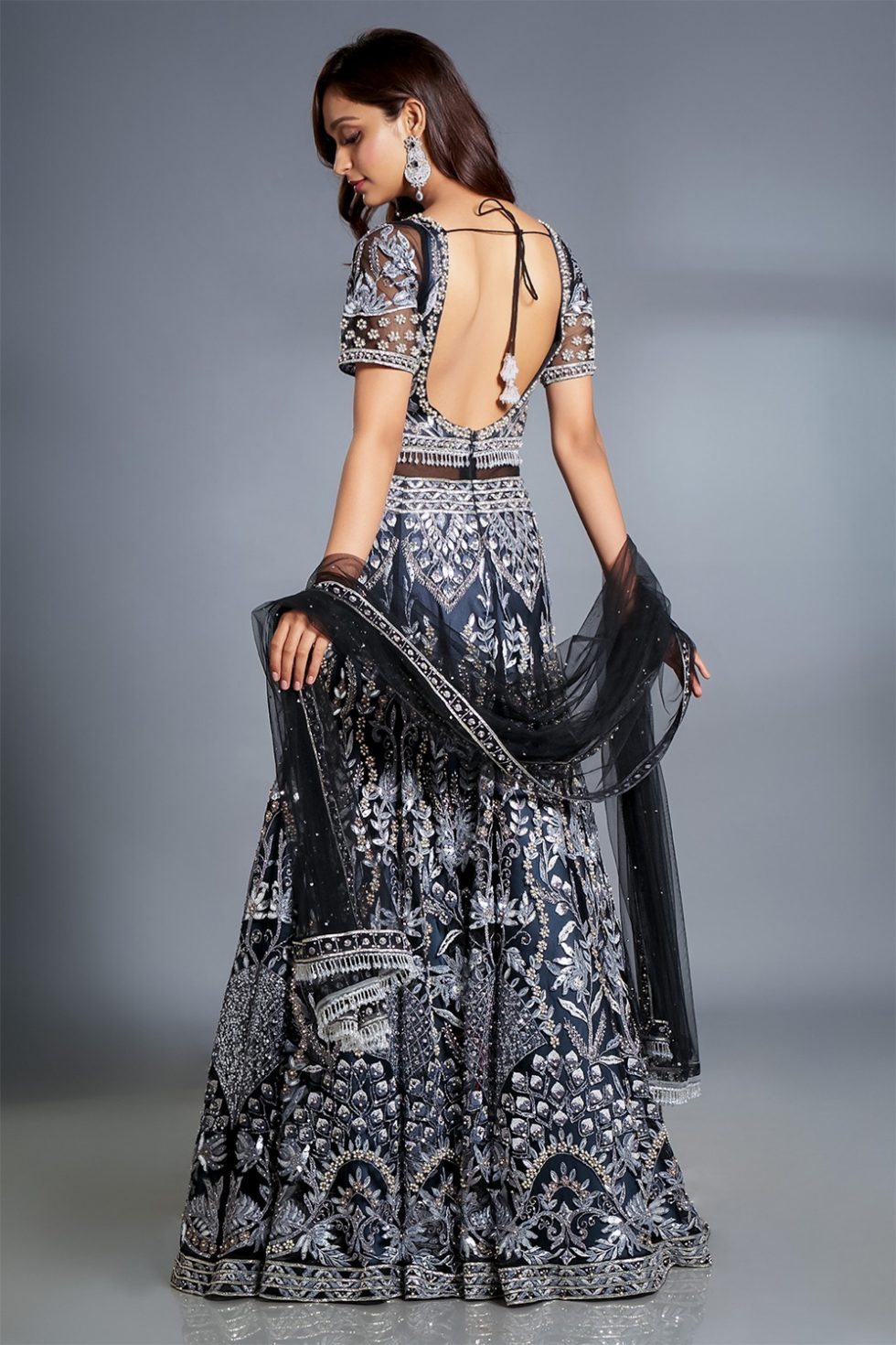 Charcoal black cut out gown set embroidered with shades of grey and silver paired with a matching dupatta and tassels.