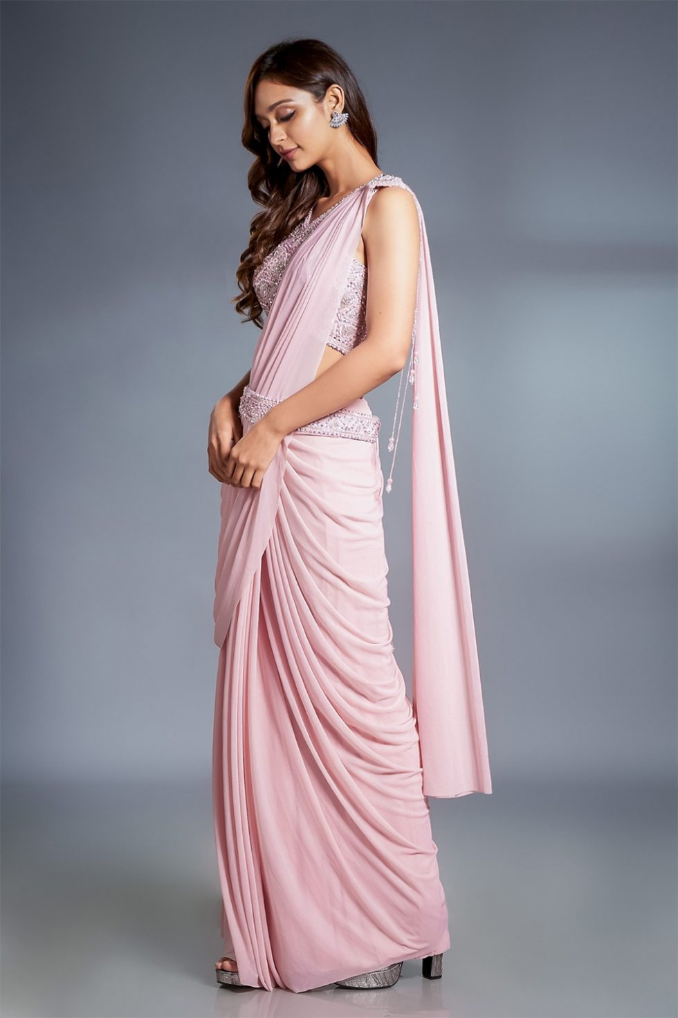 Petal pink pre stitched draped saree and matching hand embroidered blouse with 'kamarbandh' and jewelled broach with tassels.