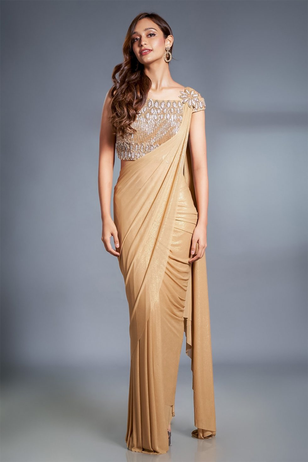 Shimmery gold pre stitched draped saree with a matching hand embroidered off the shoulder cut out back blouse and attached embroidered broach.