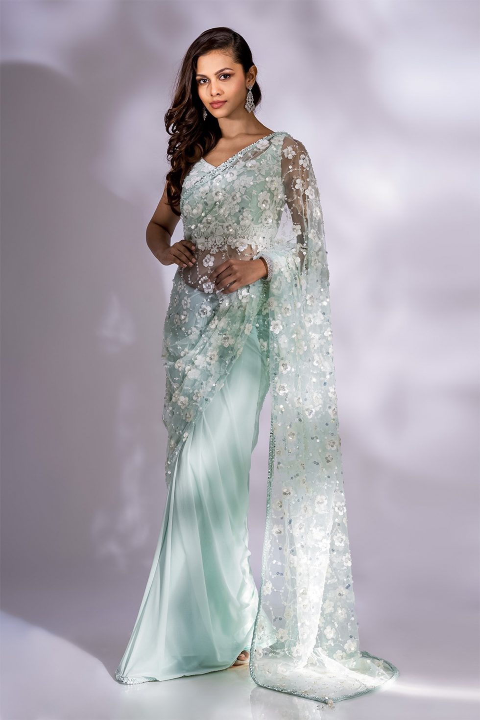 Glacial green classic saree with 3D pearl white embroidery paired with a matching blouse with threadwork and lace hem.