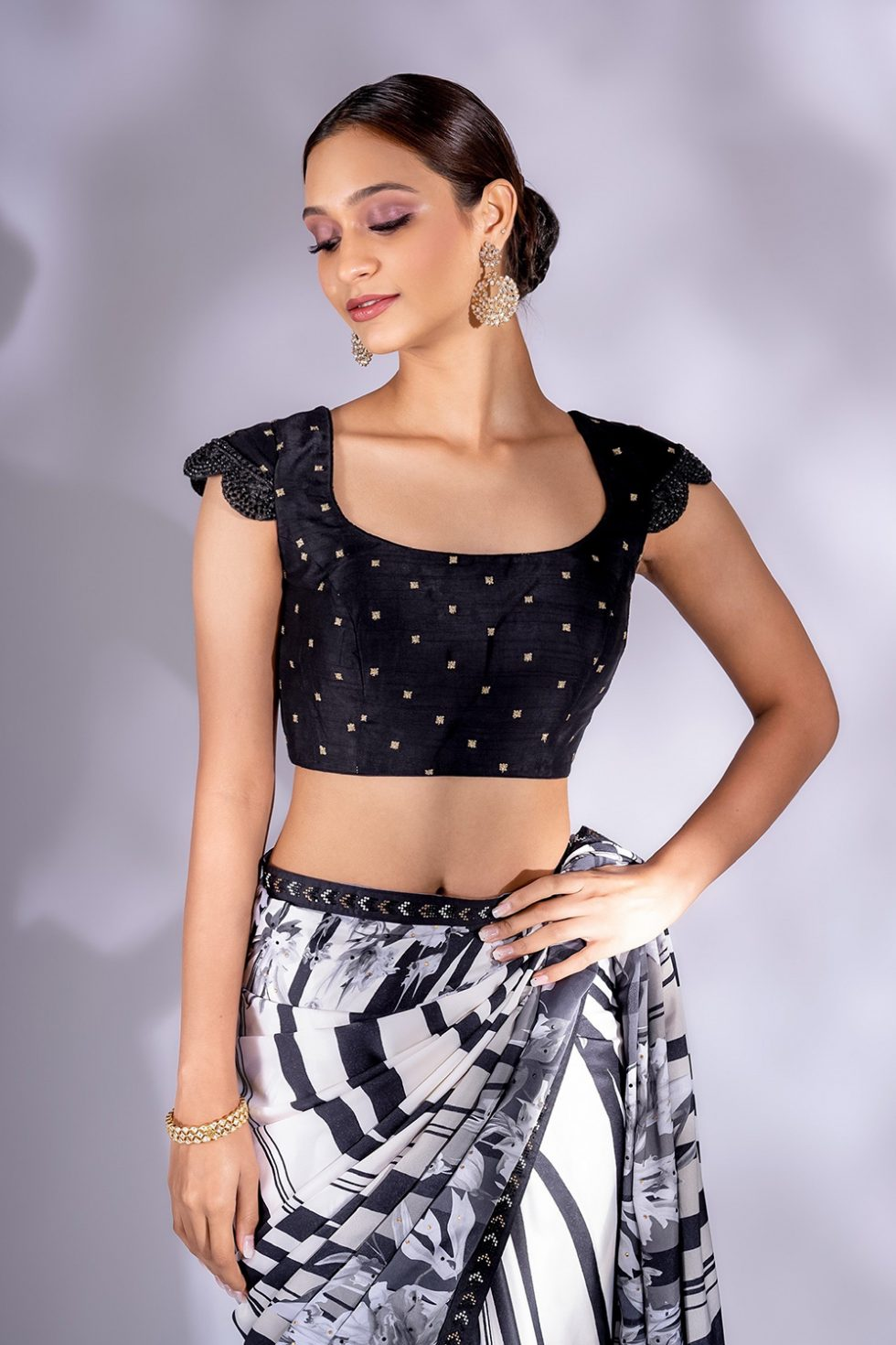 Raven black classic blouse with gold butis and scalloped sleeve detail.