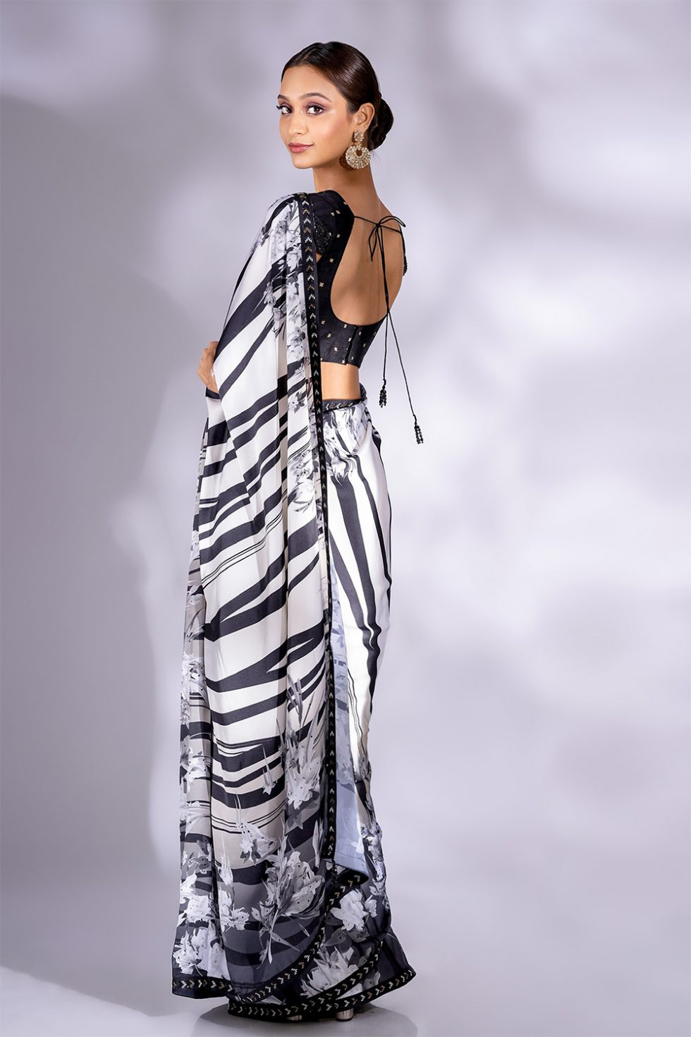 Black and white printed classic saree with an embroidered border paired with a black choli with butis and scalloped sleeve details.