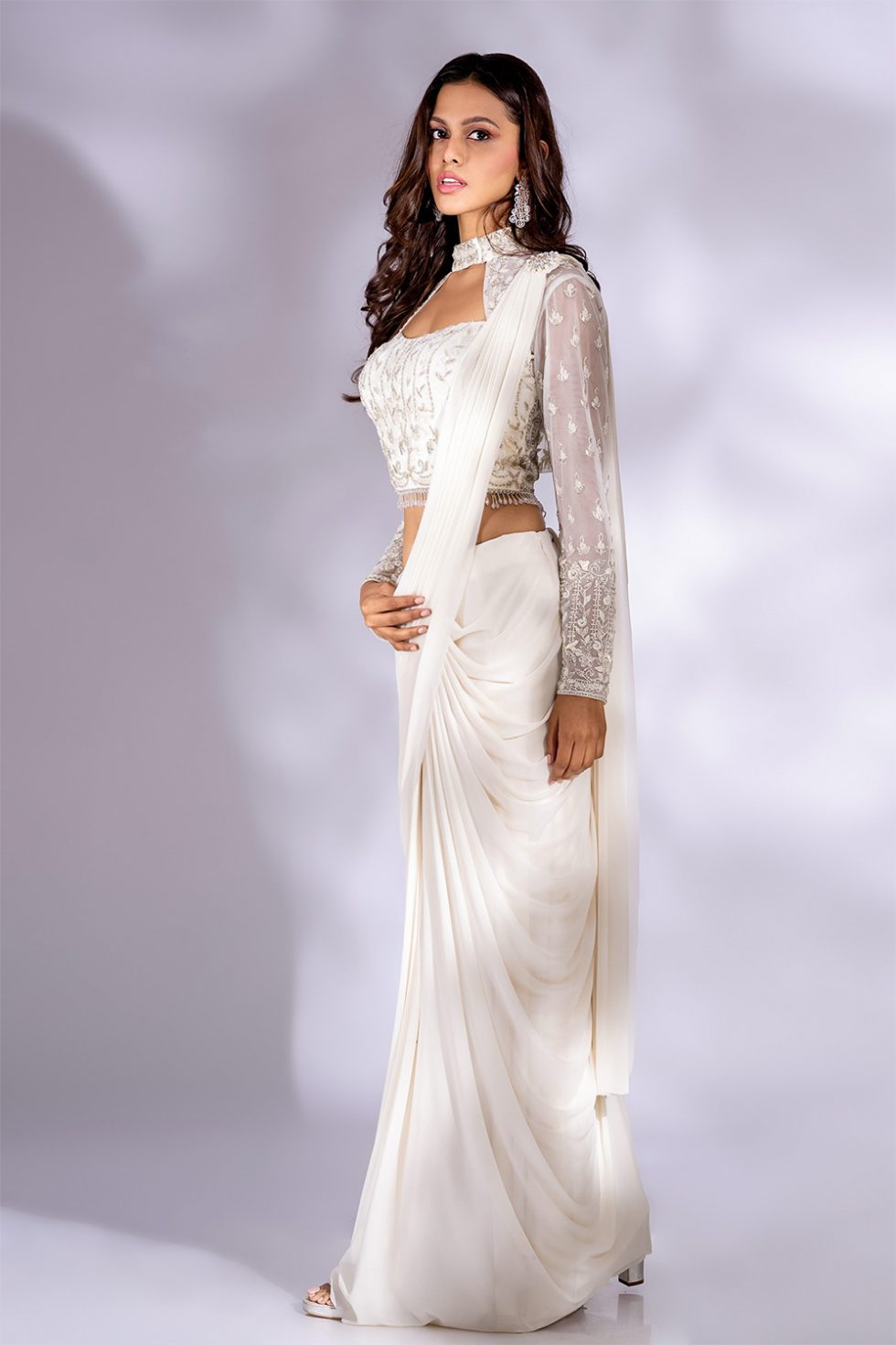 Pearl white pre stitched draped saree paired with a matching hand embroidered blouse and bolero jacket with a jewelled broach and tassels.