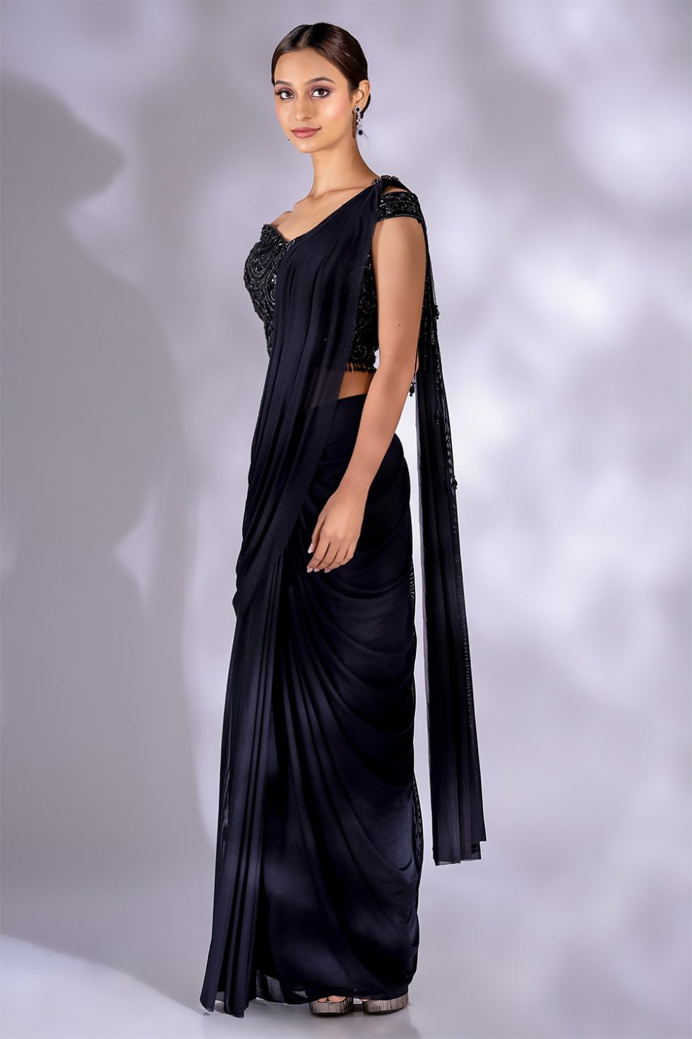 Charcoal black pre stitched draped saree and matching hand embroidered off the shoulder blouse with a jewelled broach and tassels.