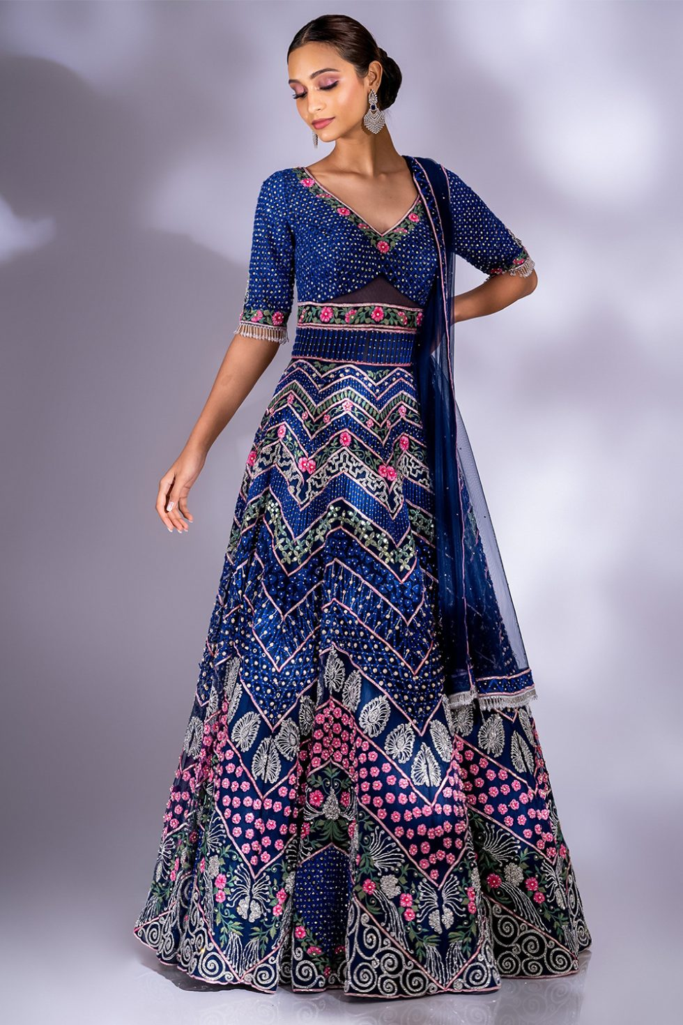Navy blue gown set with multicoloured embroidery, silver embellishments and a matching dupatta with tassels.