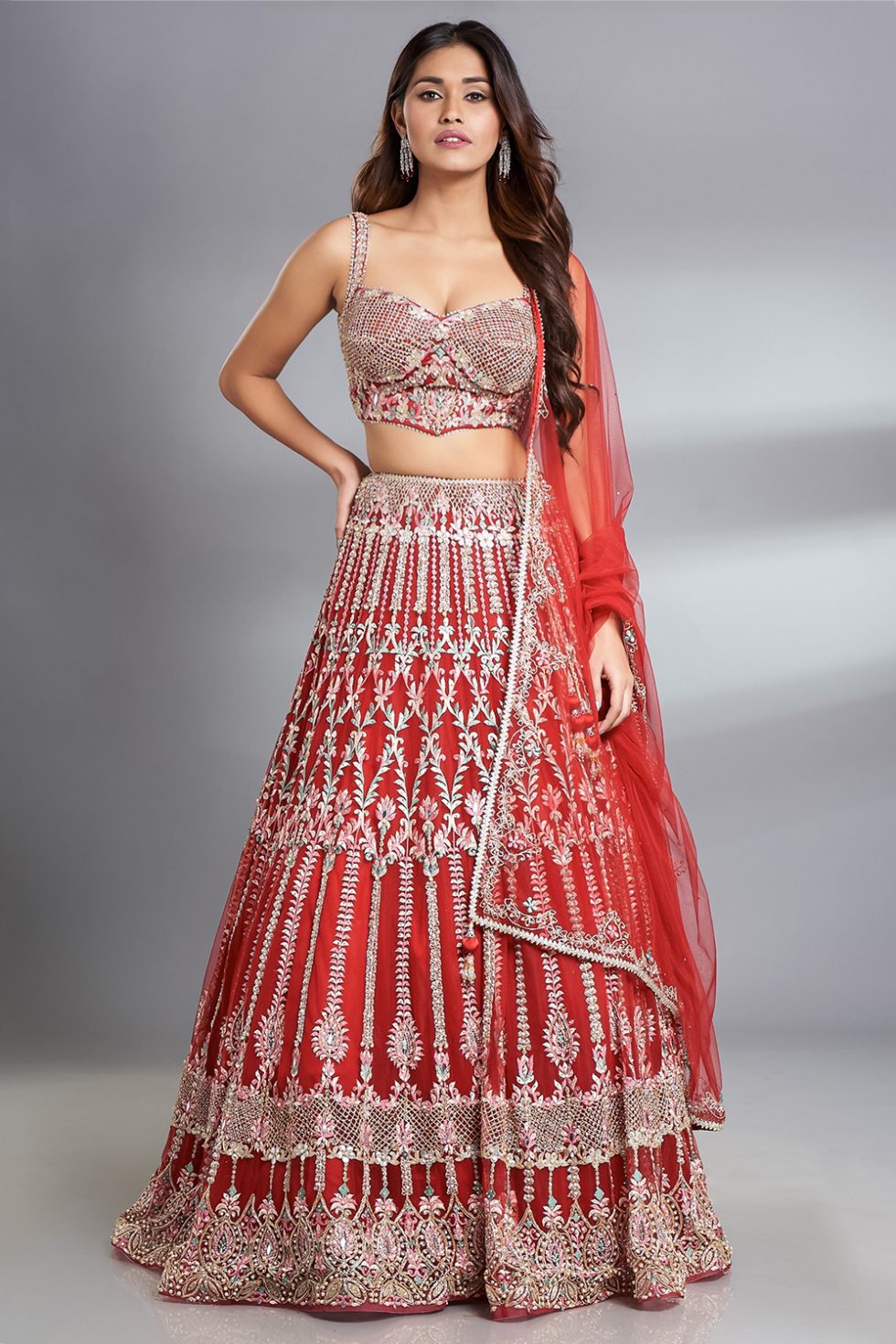 Fiery red lehenga set with multi coloured thread work and silver highlights paired with a corset cut blouse and a matching dupatta.