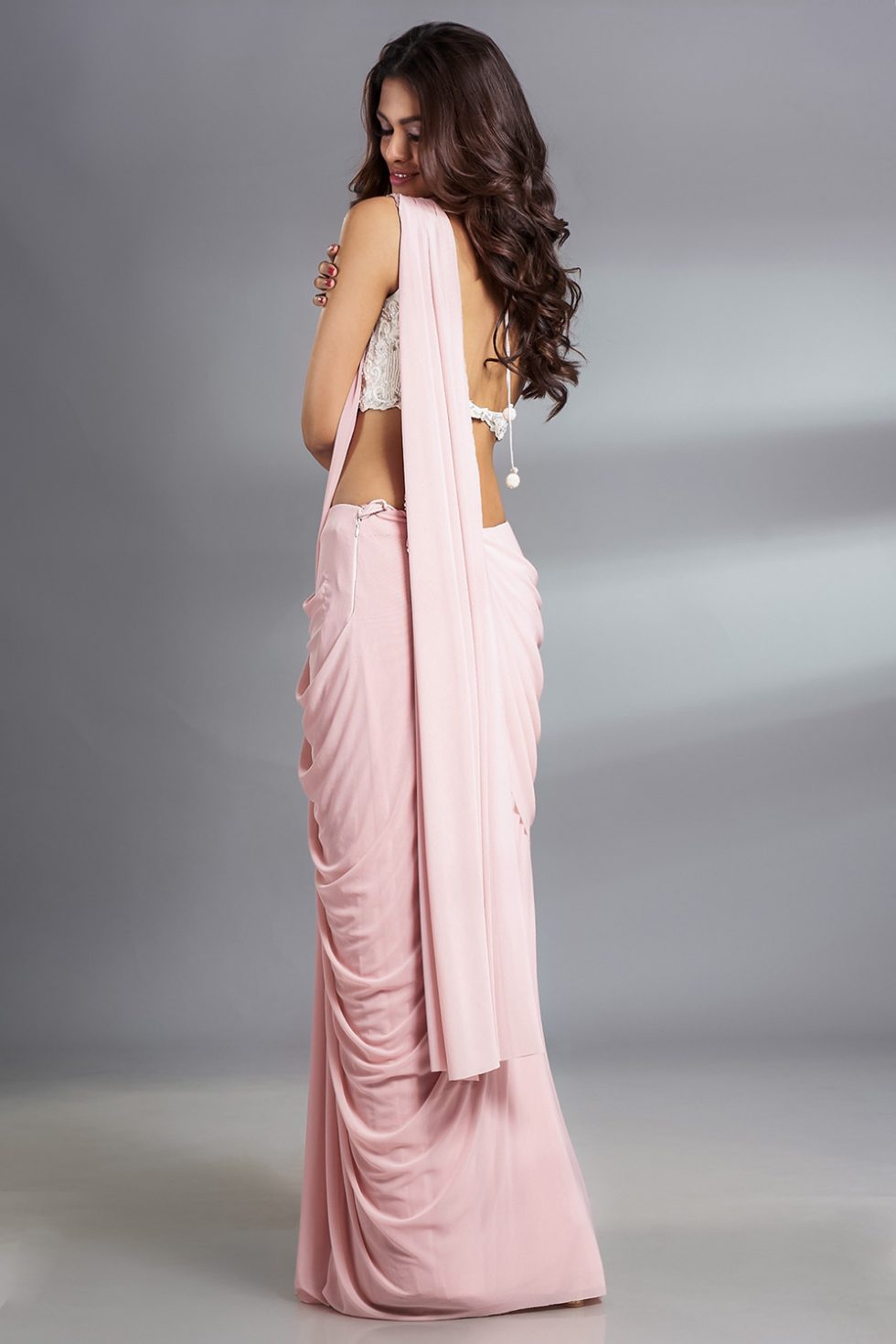 Baby pink pre stitched draped saree and ivory white hand embroidered blouse with a matching broach and tassels.