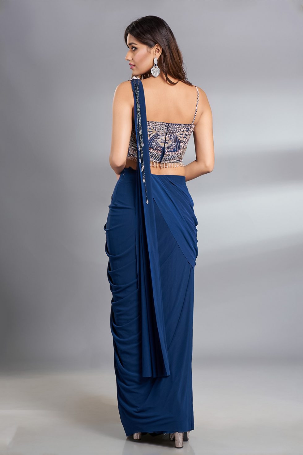 Deep blue pre stitched draped saree and  a cut out blouse with multi coloured contrast hand embroidery and a matching broach and tassels.