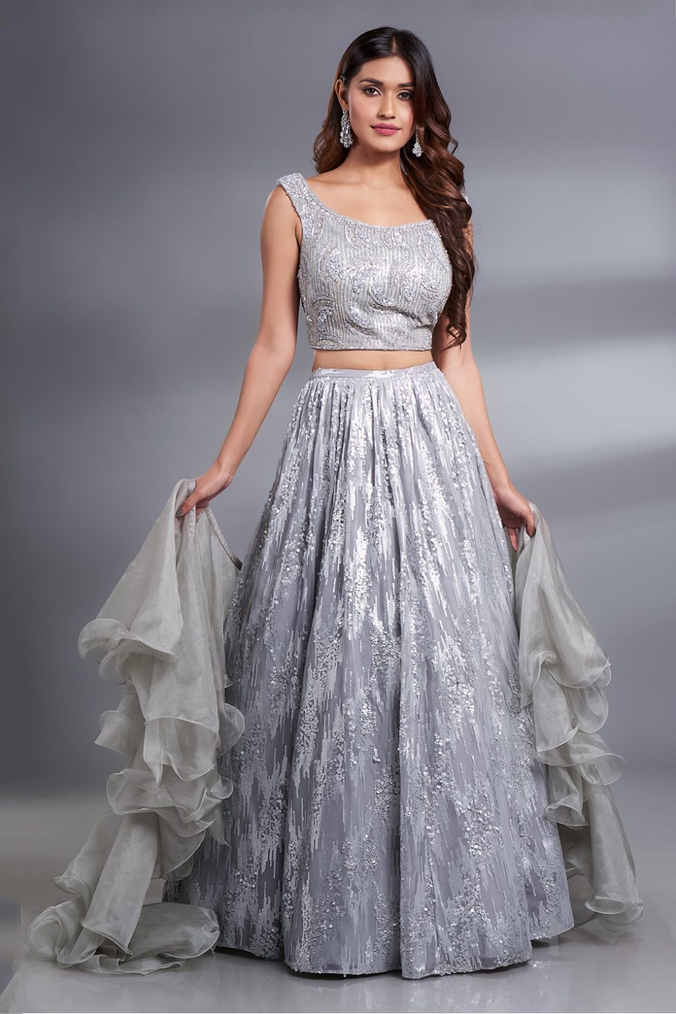 Silver grey shimmery lehenga set with a hand embroidered blouse paired with a ruffled dupatta and silver embellishments.