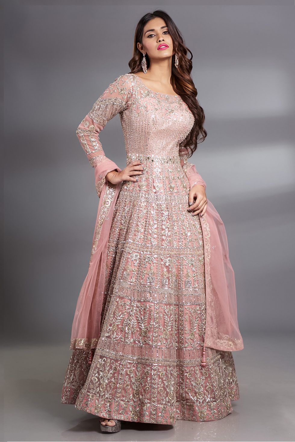 Peachish pink Anarkali gown set with silver embroidery and embellishments paired with a matching dupatta with butis.