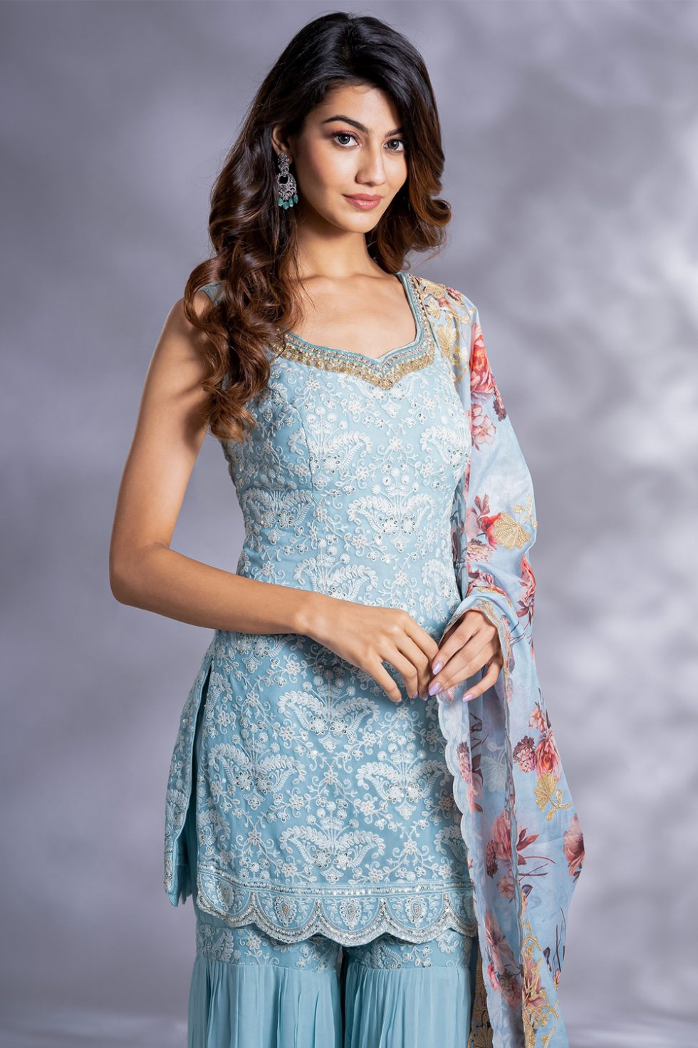 Powder blue tiered sharara pant set with a chikan kurta top paired with a printed dupatta with gold embellishments.