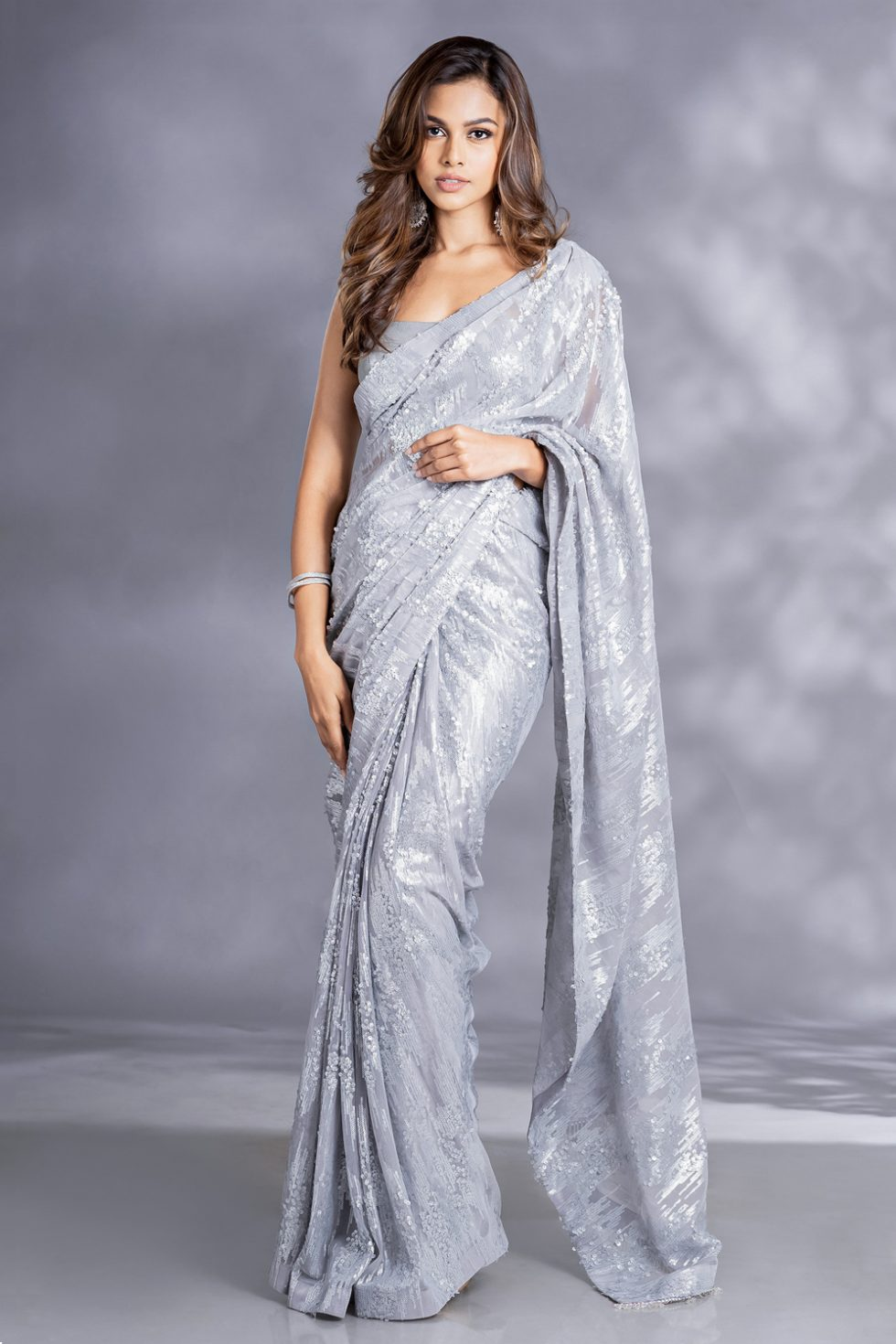 Steel grey classic saree with sequin work paired with a matching sequin classic blouse and silver tassels.