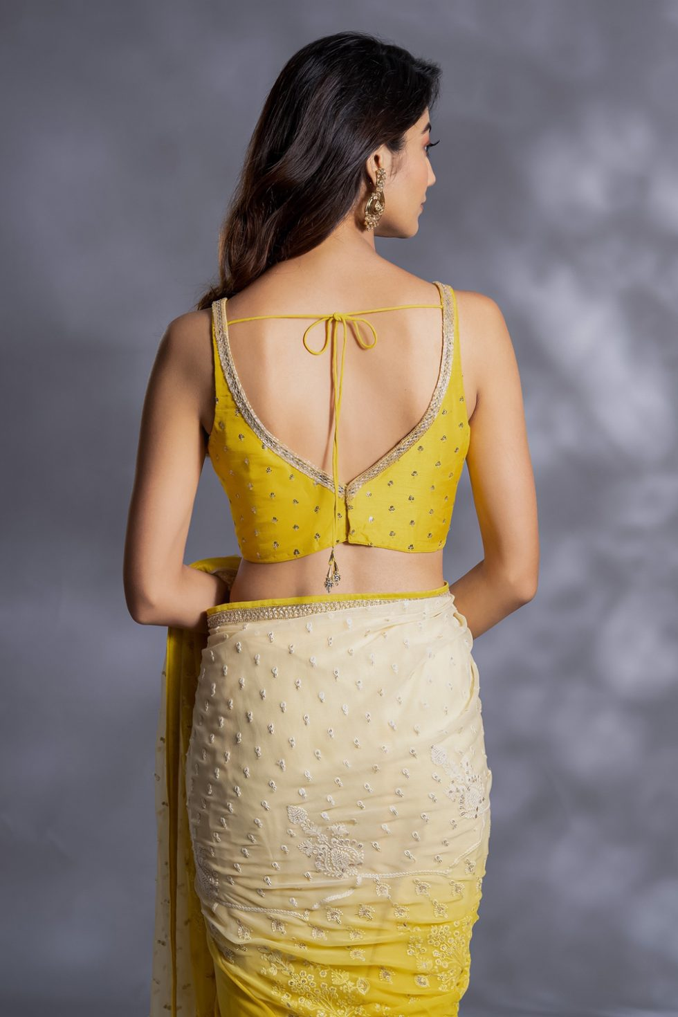 Ivory to bright yellow classic saree with a chikan pallu paired with a matching yellow blouse with gold butis.