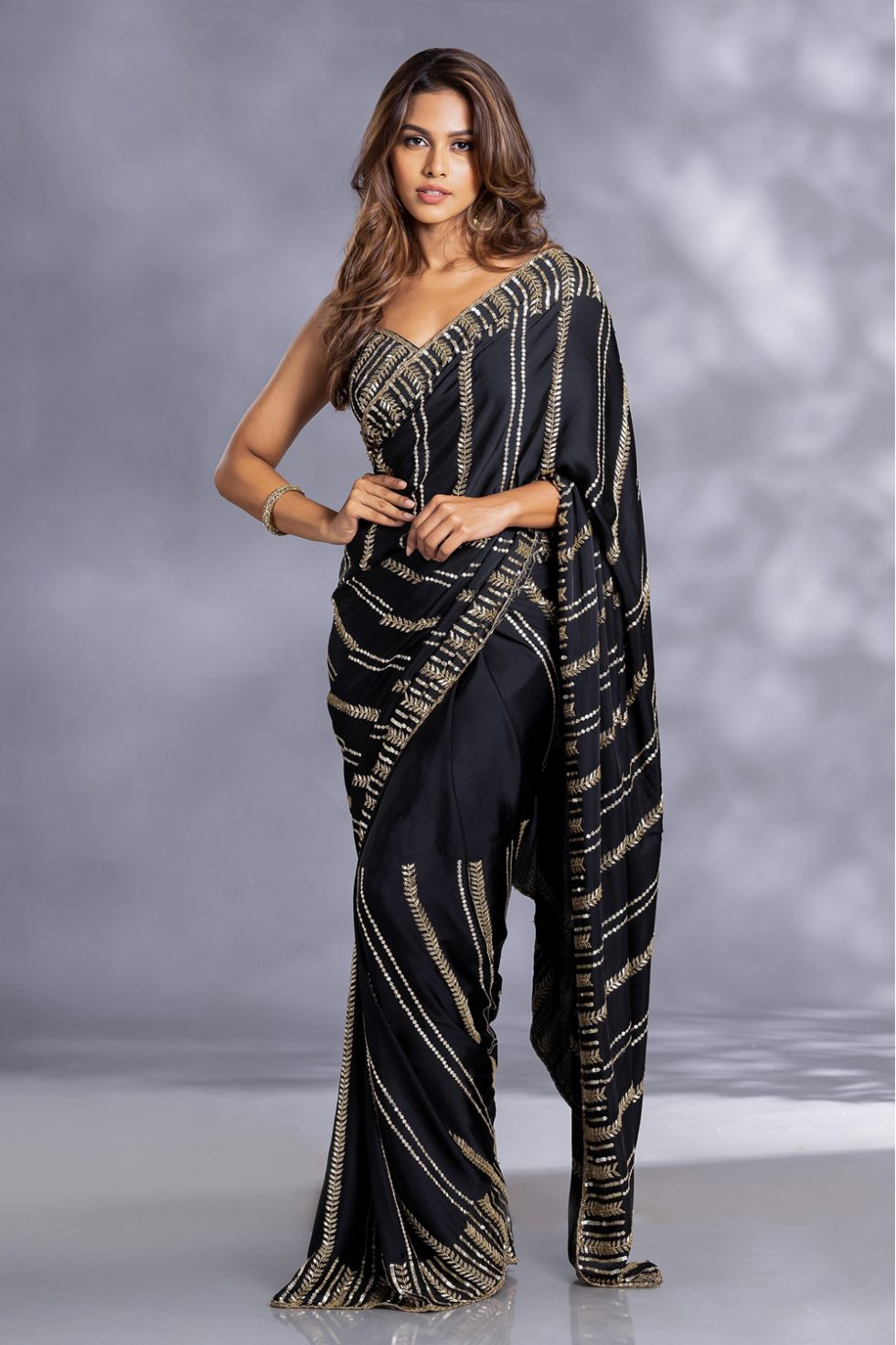Raven black classic cocktail saree with dull gold zardozi embroidery paired with a matching hand embroidered blouse and gold tassels.