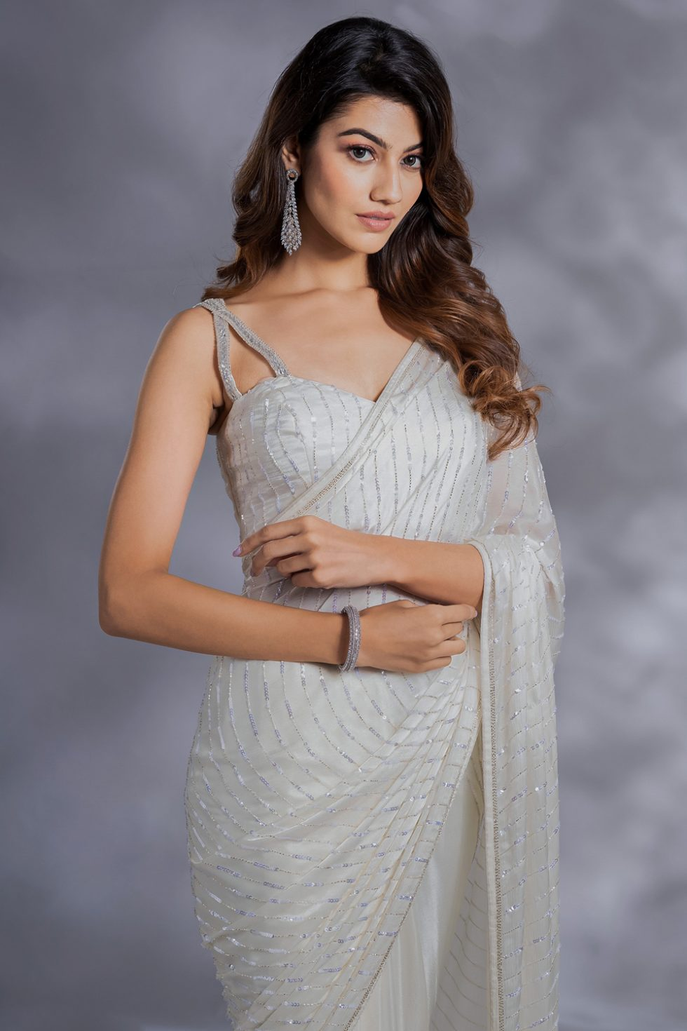 Ivory white classic half and half saree with sequin work paired with a matching blouse with embroidered straps