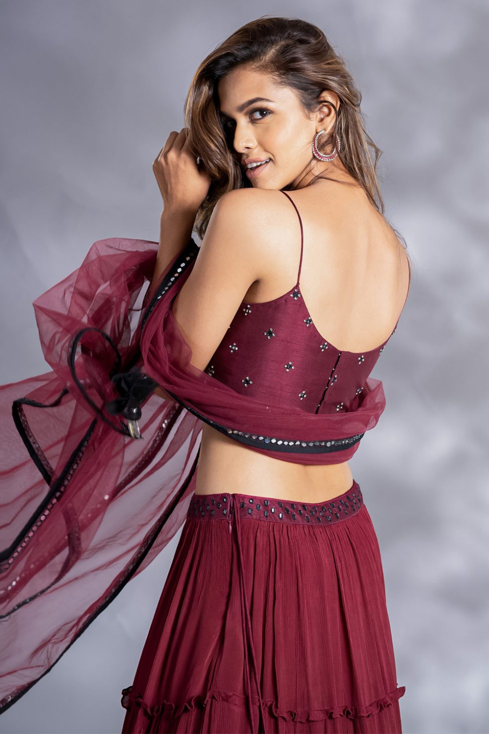"""Deep maroon tiered lehenga set with a charcoal antique hand embroidered """"abla"""" strappy blouse paired with a matching dupatta."""