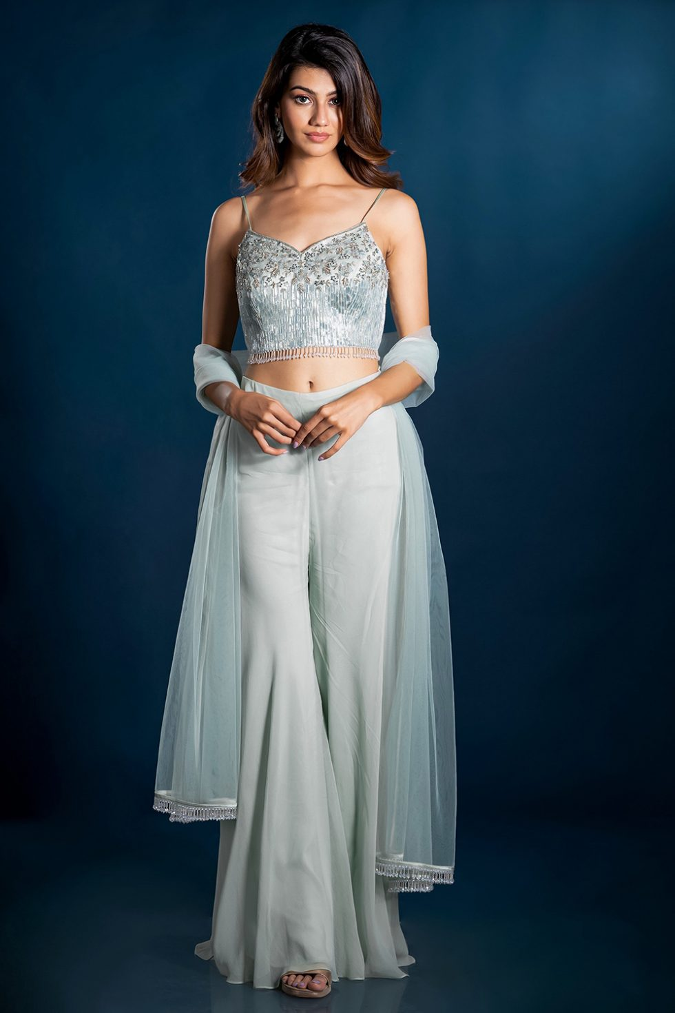 Pastel green palazzo pant set with a hand embroidered blouse and silver embellishments paired with a matching dupatta and tassels.