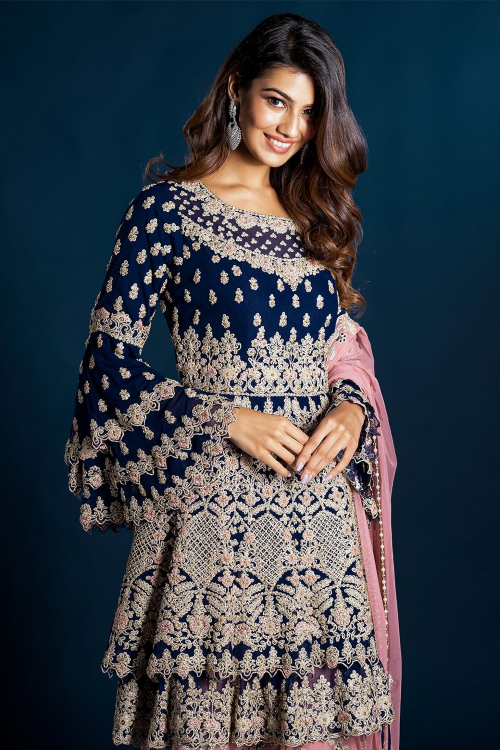 Navy blue tiered kurta top and contrast pink sharara pants with coloured embroidery paired with a matching dupatta.