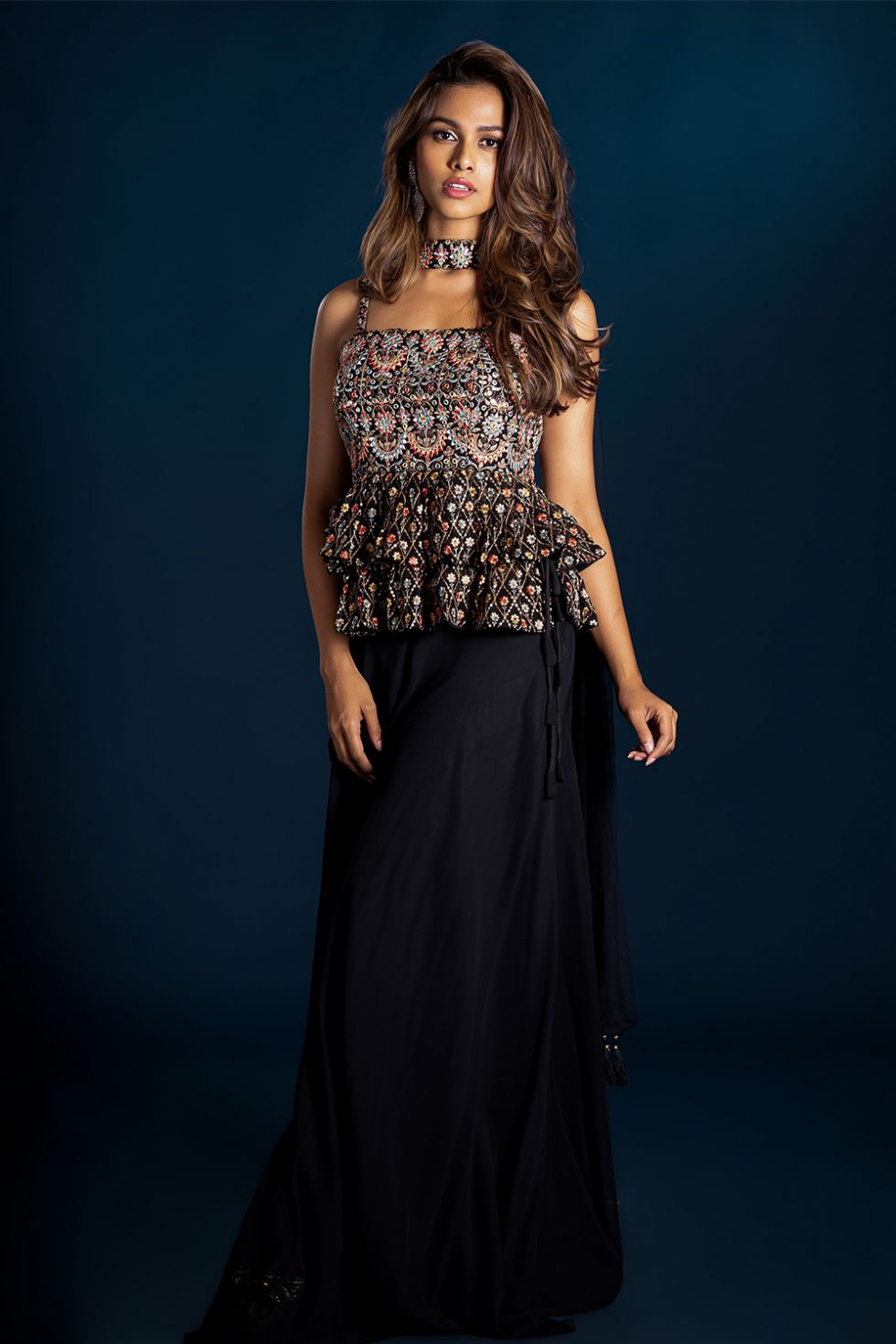 Jet black palazzo pant set with a tiered multi coloured thread work peplum top paired with a matching necklace style dupatta.