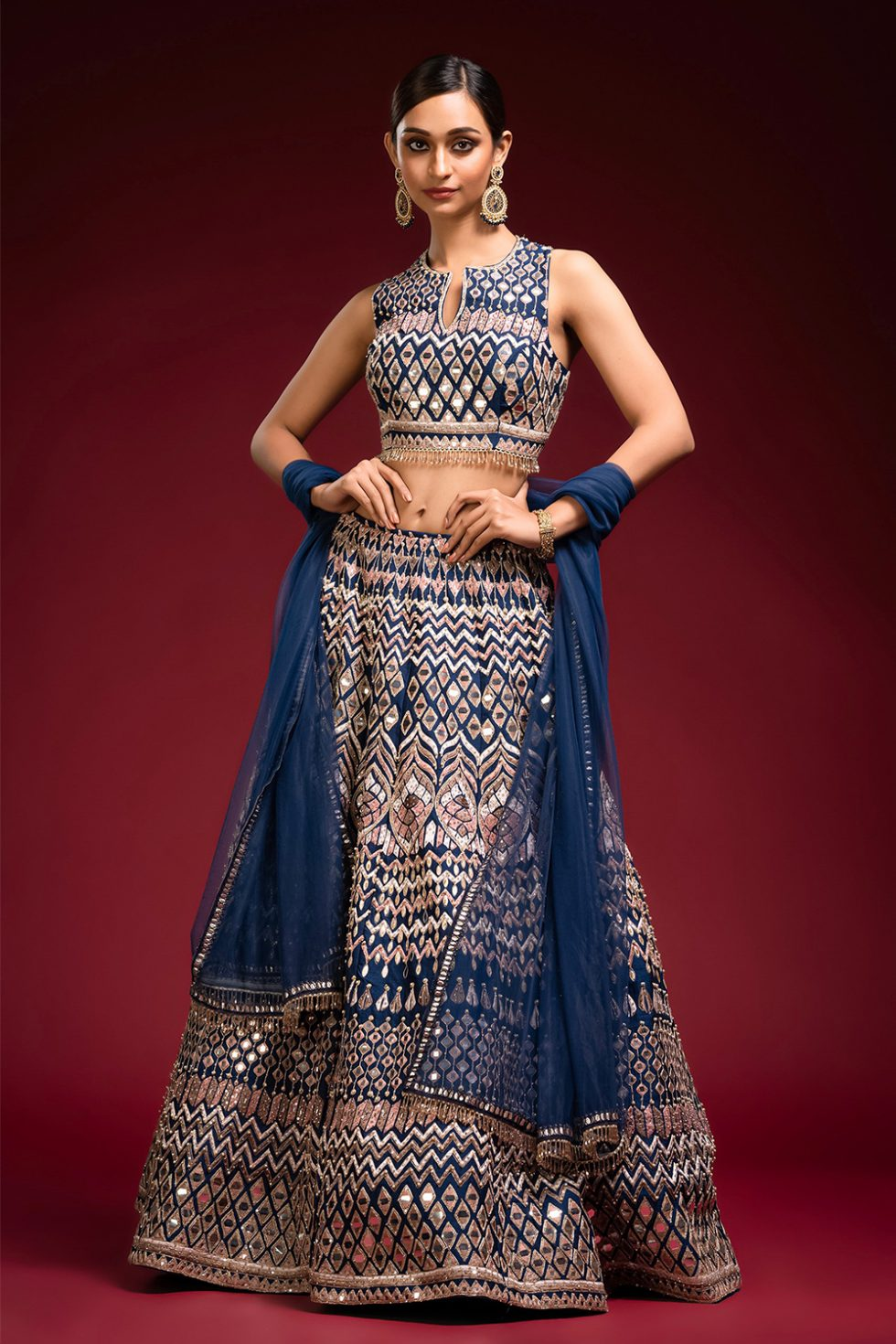 """Deep blue lehenga set with multi coloured embroidery and """"abla"""" paired with a matching dupatta and tassels."""