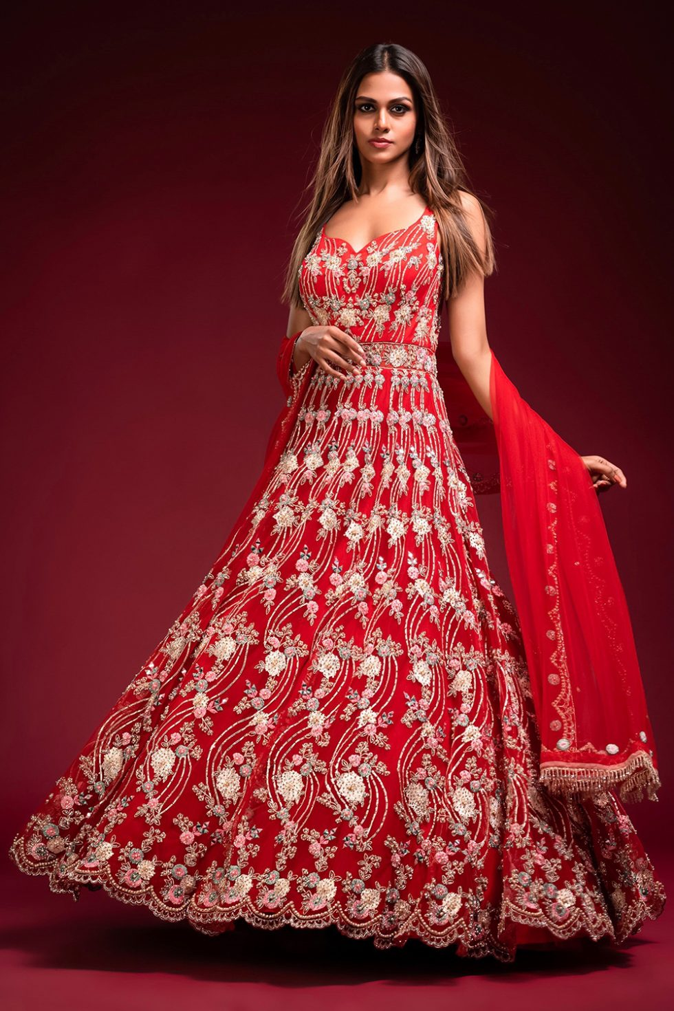 """Fiery red gown set with multi coloured embroidery and """"abla"""" paired with a matching scalloped dupatta and gold embellishments."""