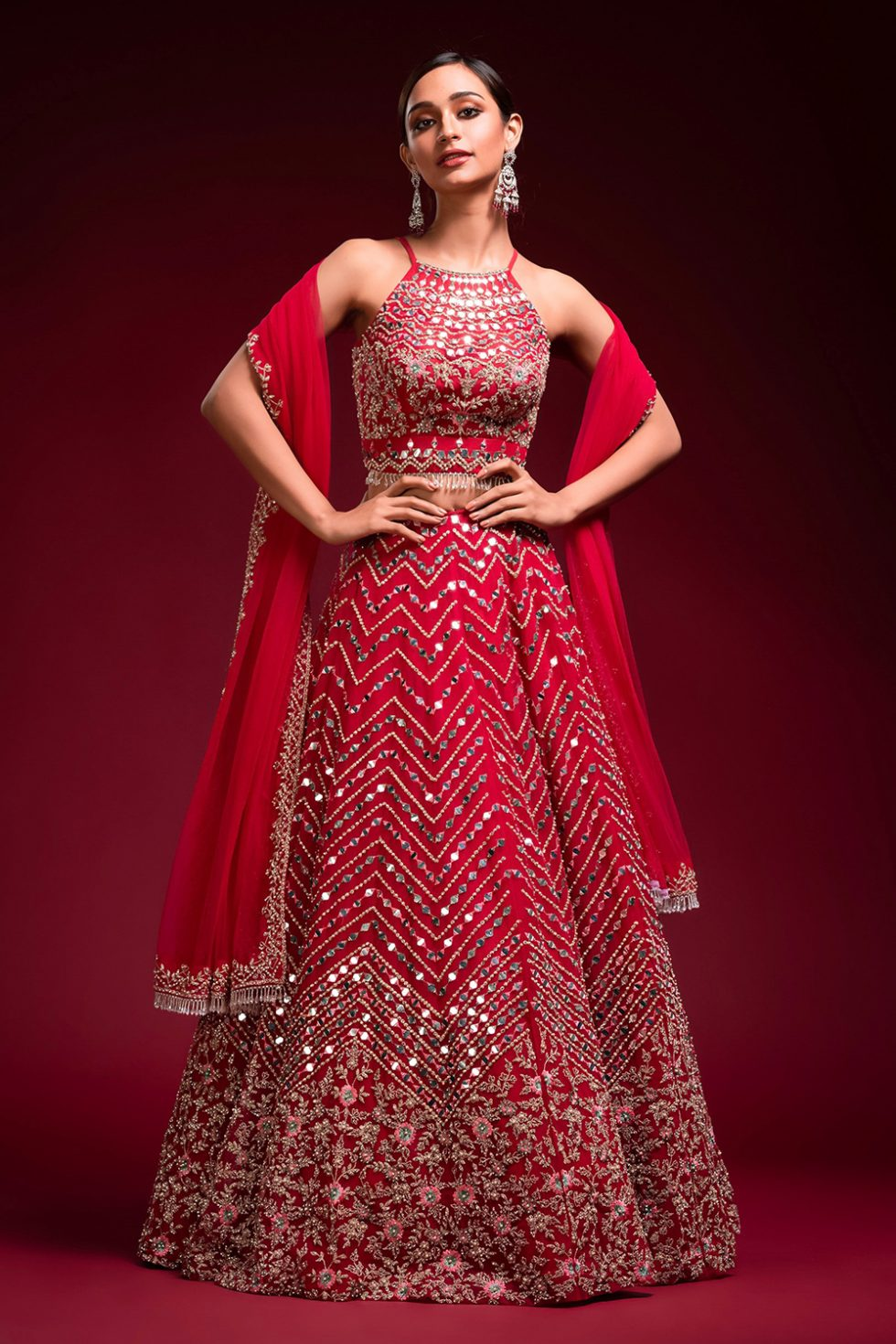"""Cherry red lehenga set with multi coloured embroidery and """"abla"""" paired with a matching dupatta, gold embellishments and tassels."""