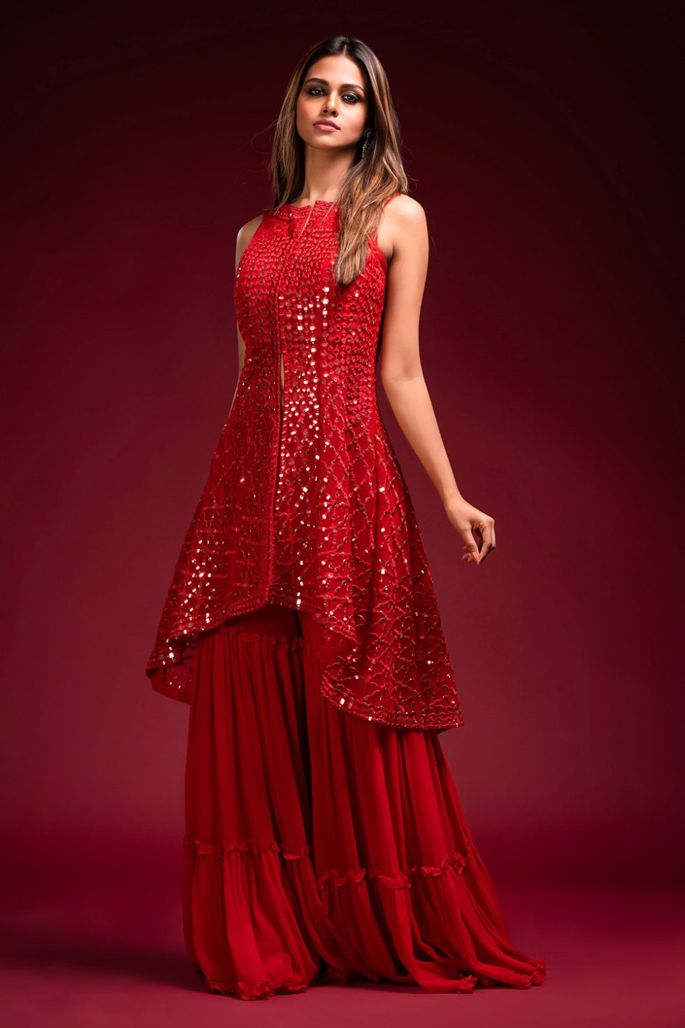 """Bright red tiered sharara set with a high low hem jacket style kurta top with """"abla"""" work."""