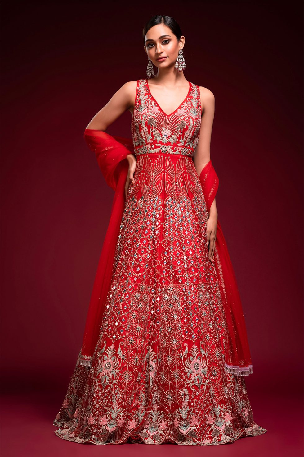 """Apple red gown set with multi coloured embroidery, gold and silver embellishments and """"abla"""" paired with a matching dupatta and tassels."""