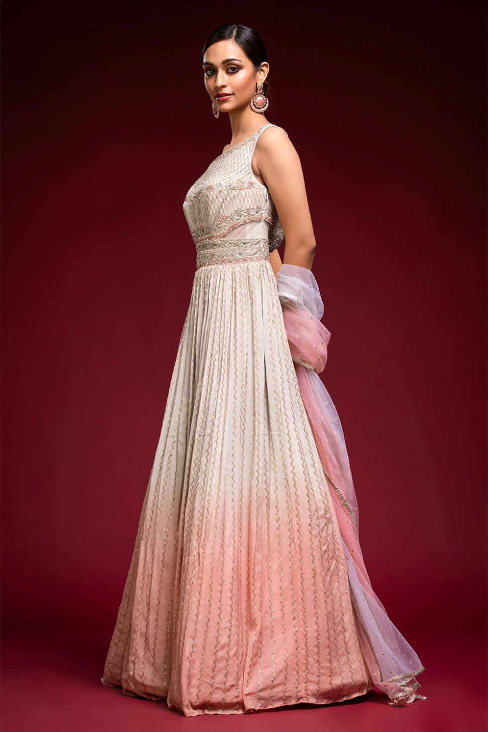 Ombré pastel grey to blush pink gold geometric patterned Anarkali gown set with a hand embroidered cut out bodice paired with a matching shaded dupatta and gold embellishments.
