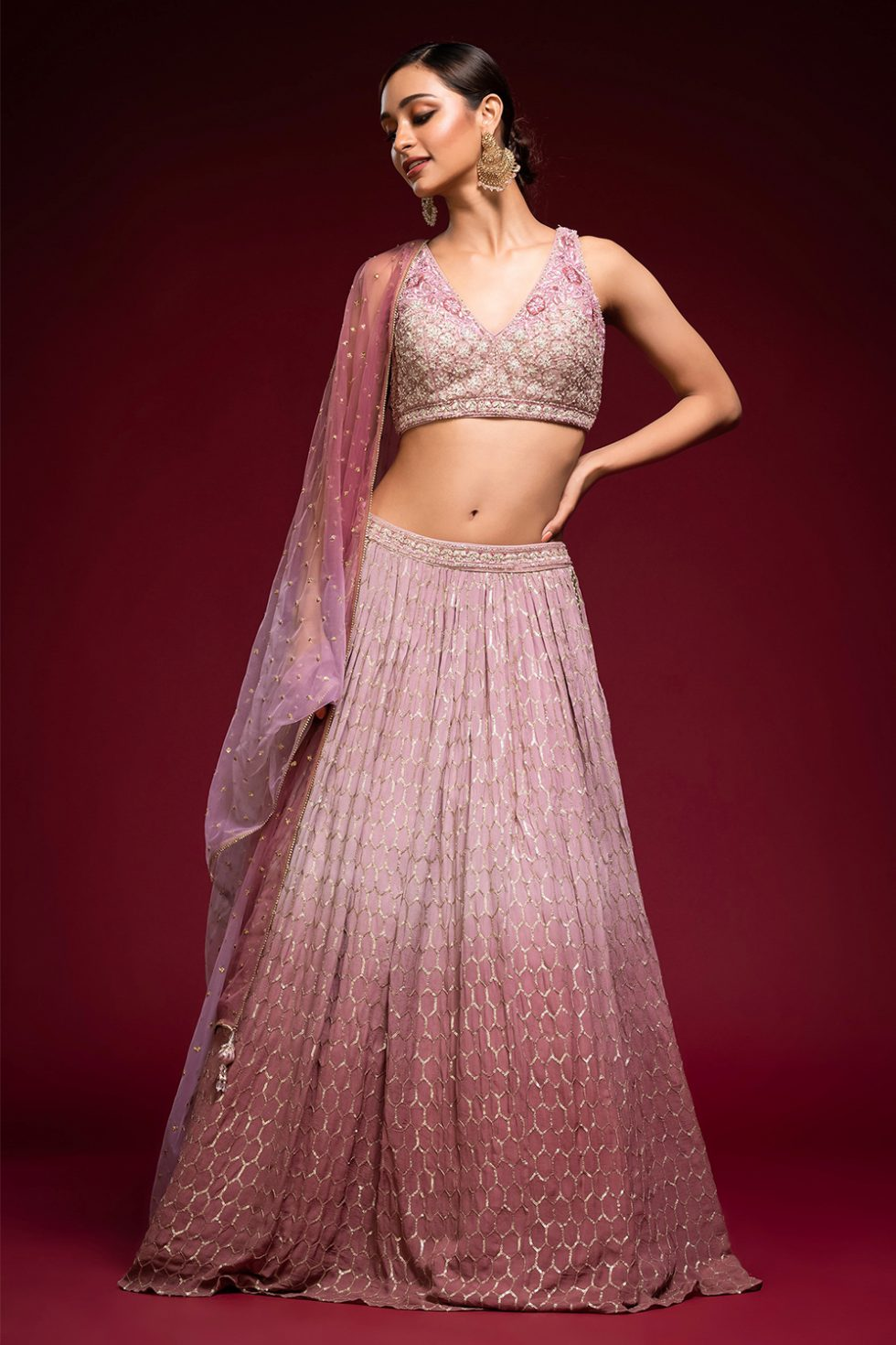 Ombré pink to pinkish purple geometric gold patterned lehenga set with an embroidered tie up blouse paired with a matching shaded dupatta and gold butis.