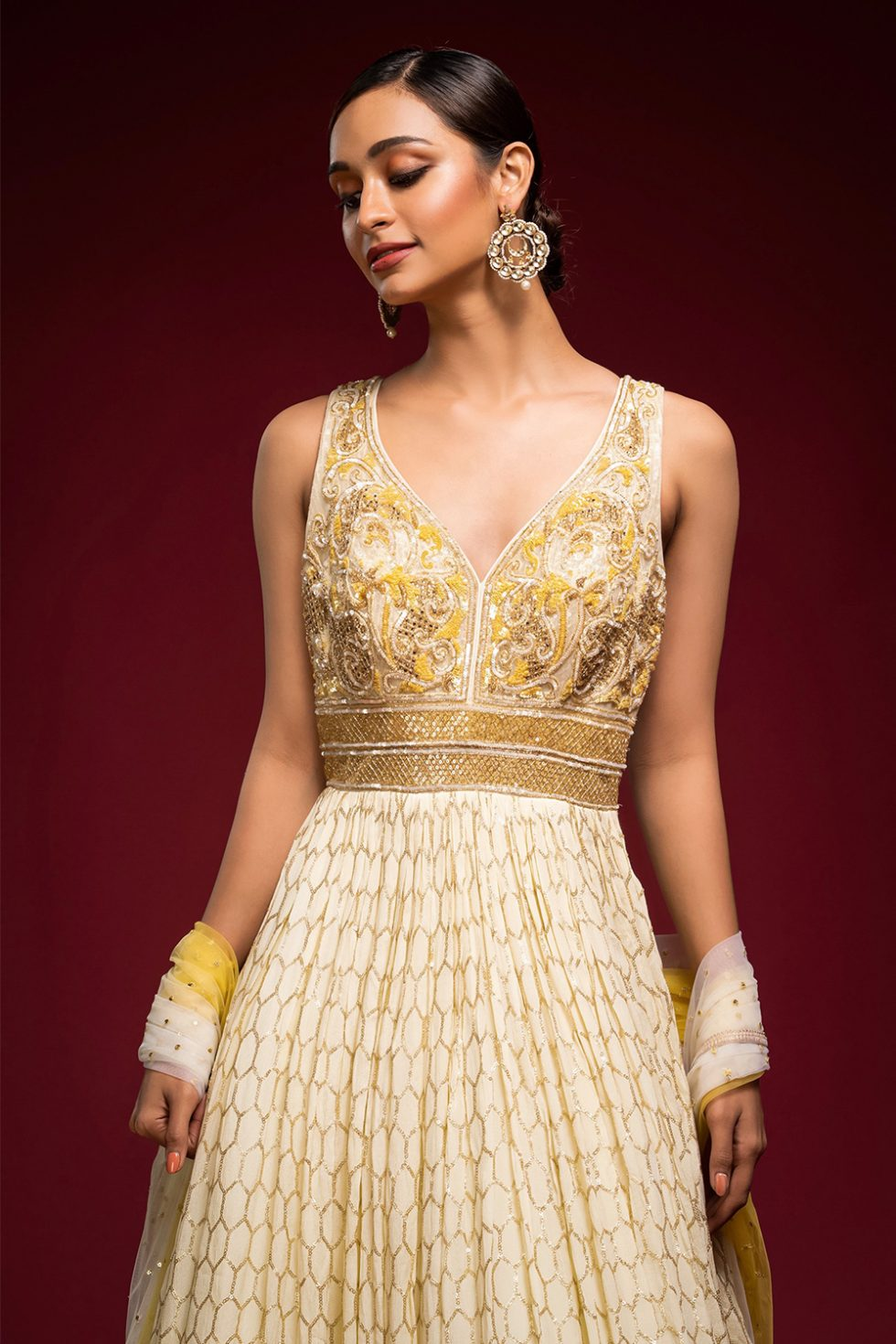 Ombré ivory to yellow gold geometric patterned Anarkali gown set with a hand embroidered bodice paired with a matching shaded dupatta and gold embellishments.