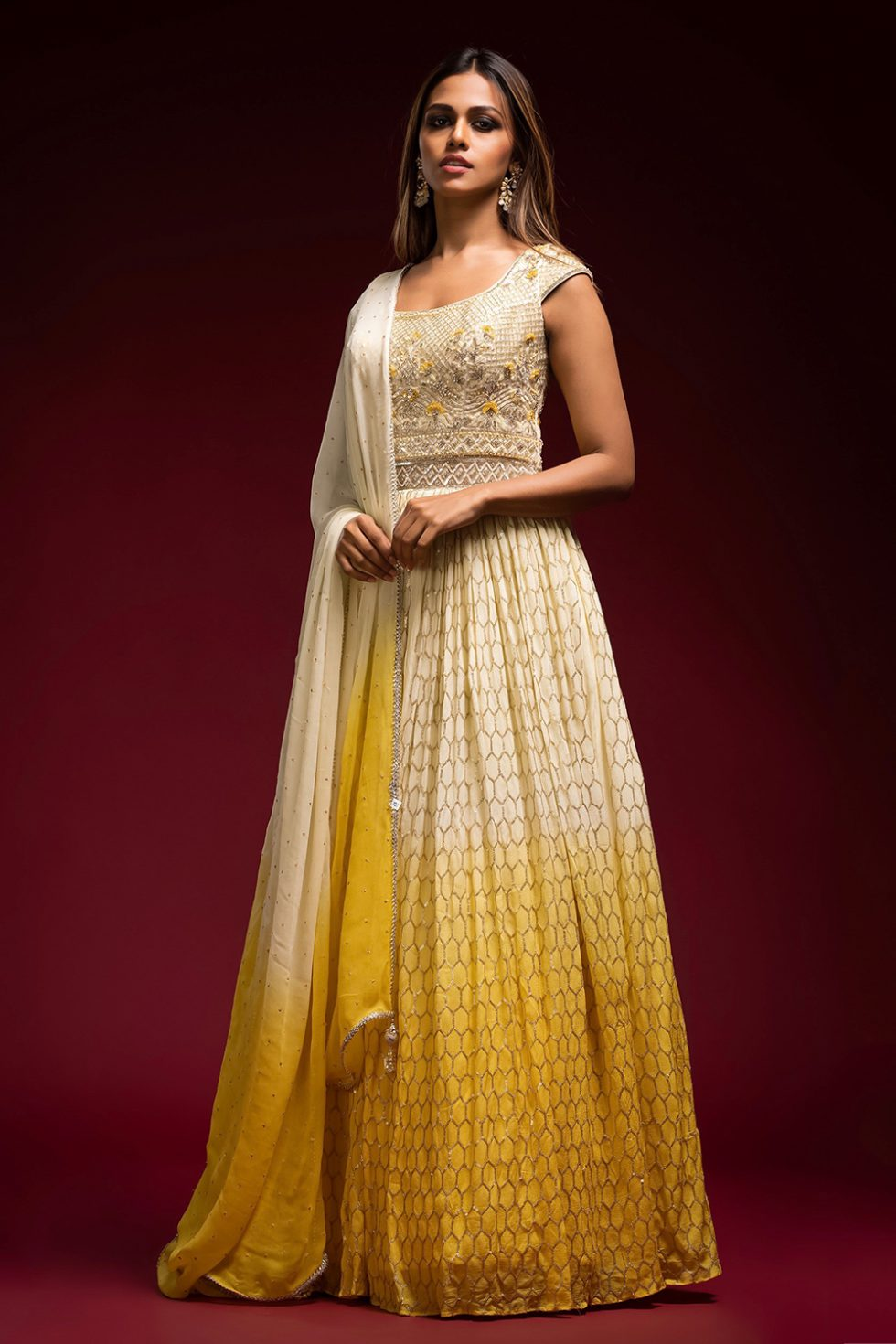Ombré cream to yellow gold geometric patterned Anarkali gown set with a hand embroidered bodice paired with a matching shaded dupatta and gold embellishments.