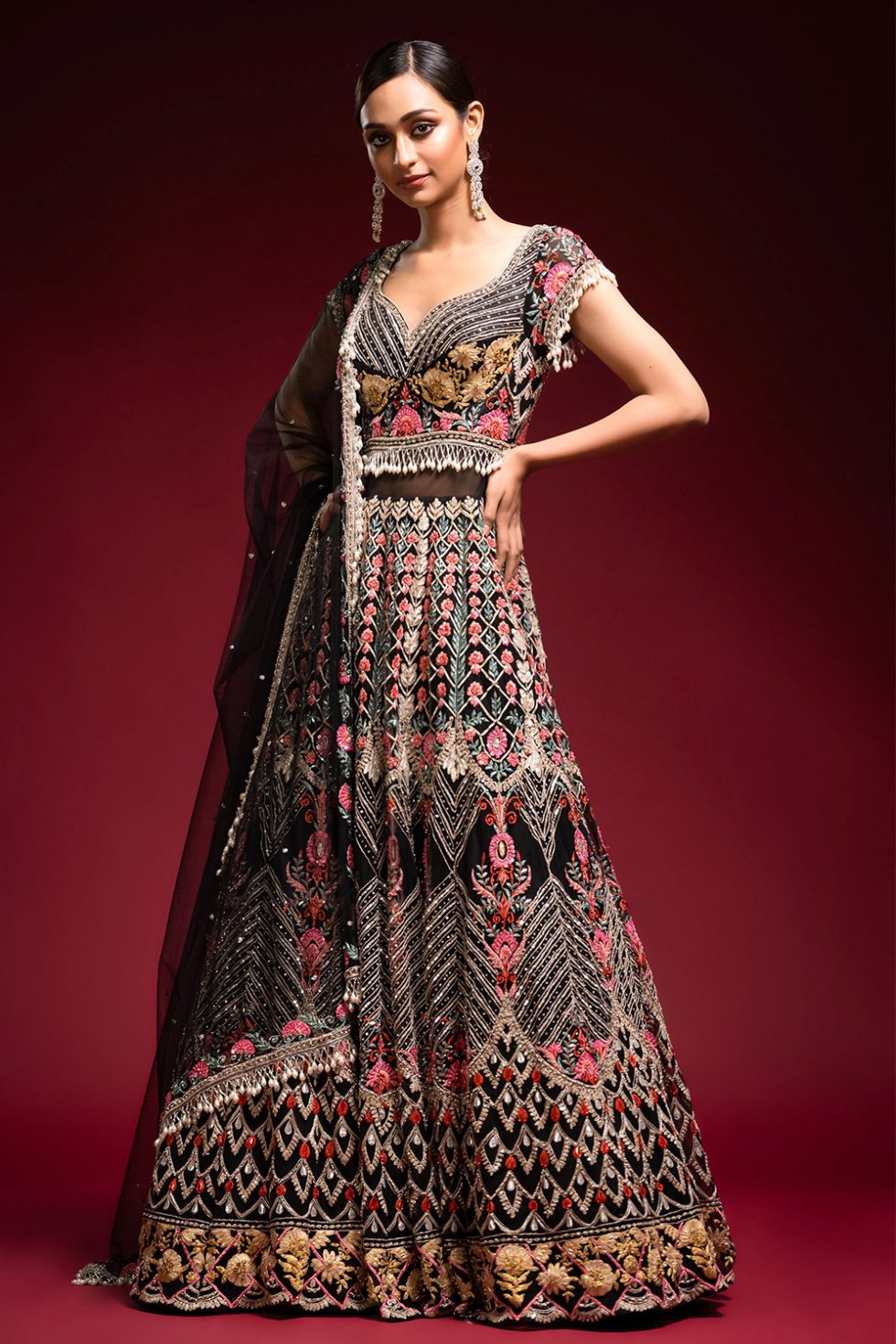 Jet black gown set with multi coloured, gold and silver embroidery paired with a matching dupatta and pearl tassels.