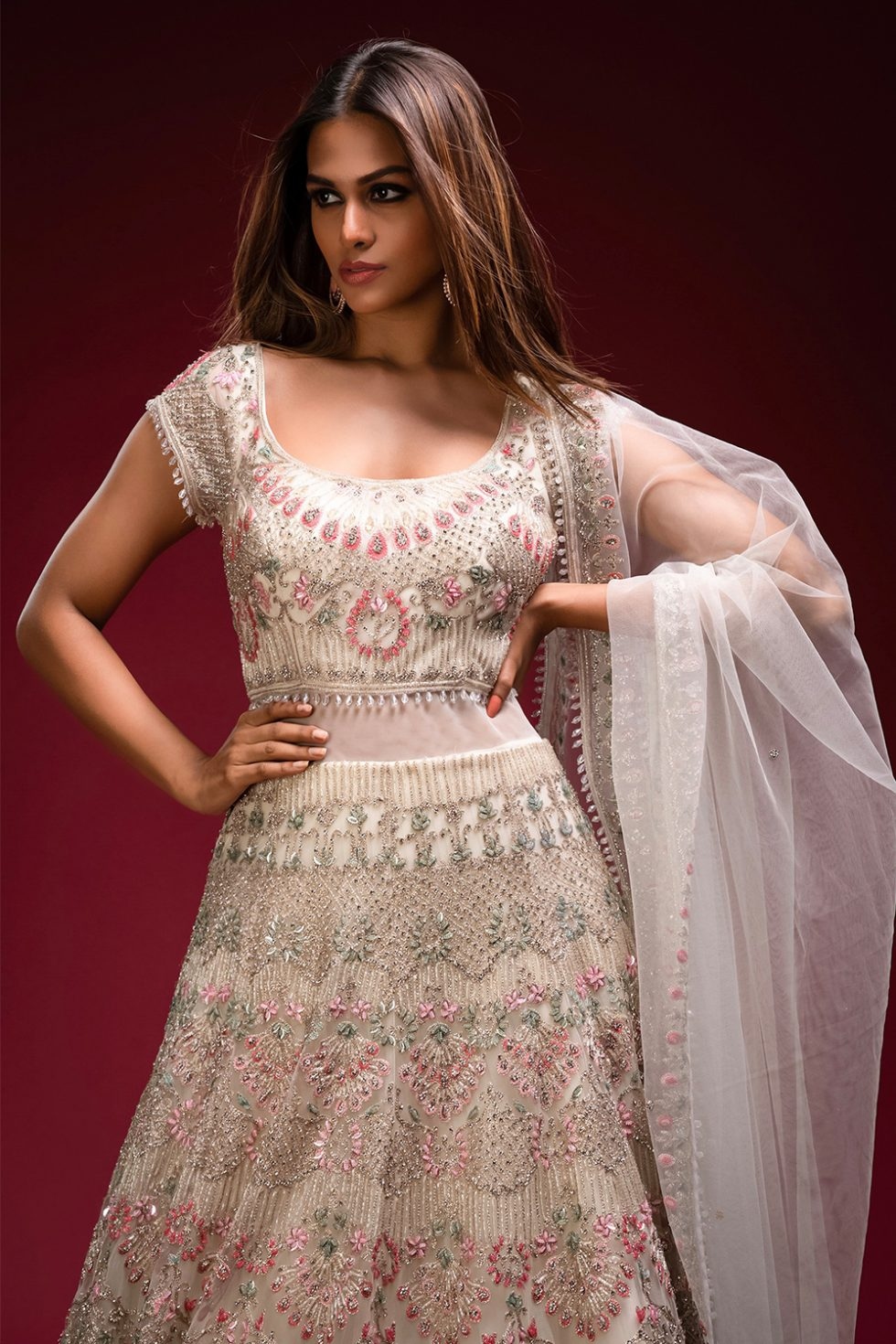 Ivory white gown set with multi coloured embroidery paired with a matching dupatta, tassels and silver embellishments.