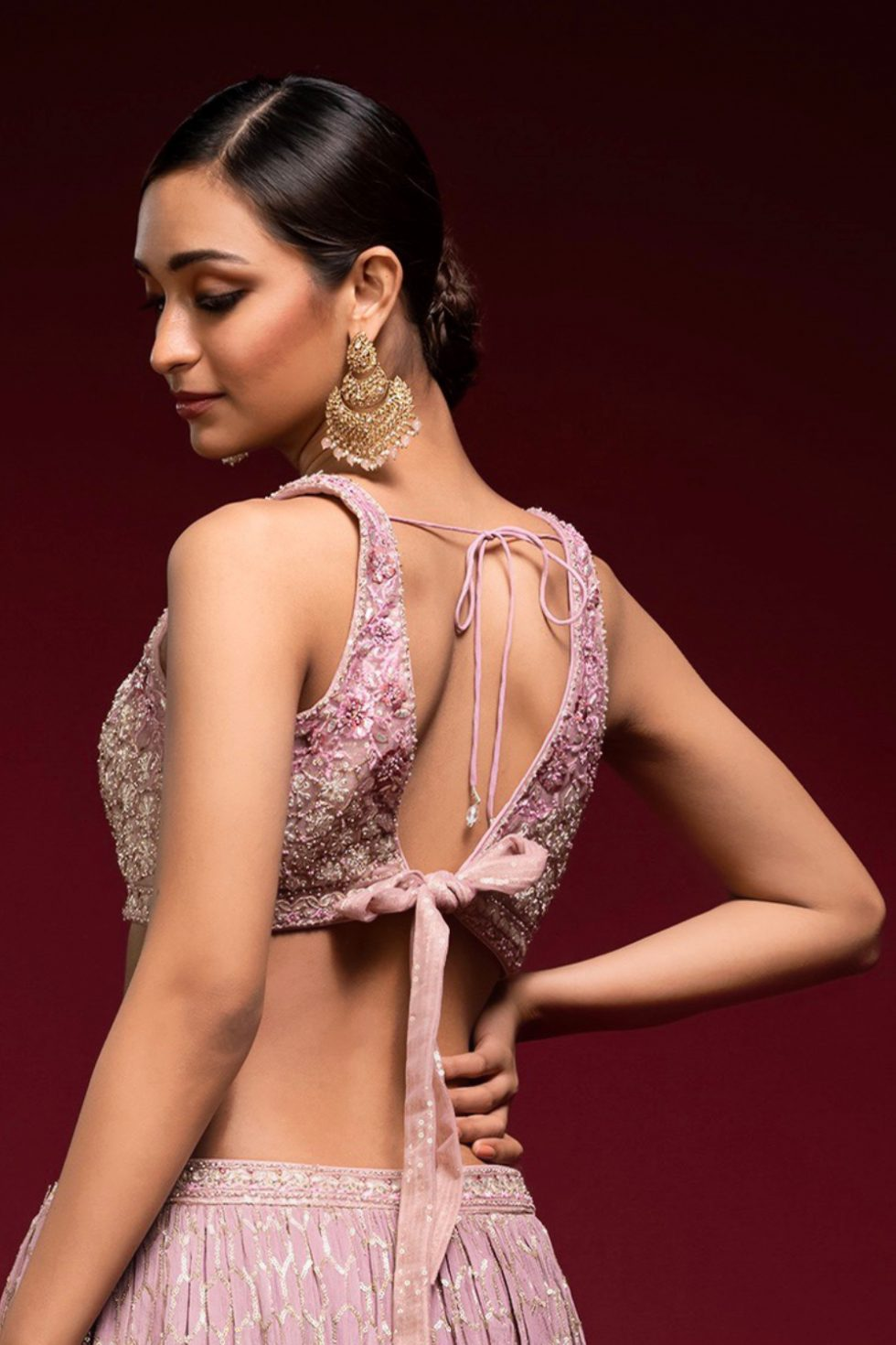 Blush pink embroidered blouse with a tie up back and gold embellishments.