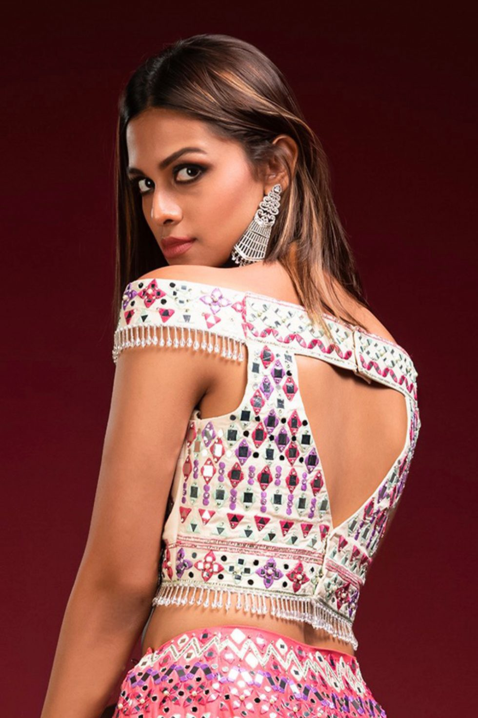 """Ivory off the shoulder blouse with multicoloured embroidery and """"abla"""" with tassels."""