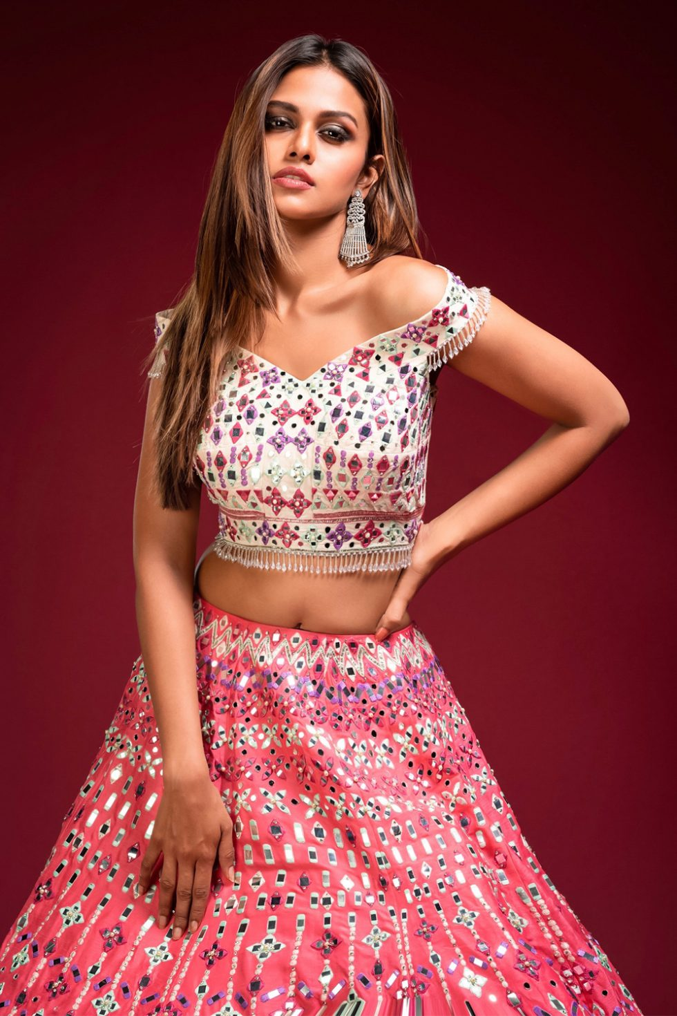 """Brick blush pink lehenga and a contrast ivory off the shoulder blouse with multi coloured embroidery and """"abla"""" paired with a matching pink dupatta and tassels"""