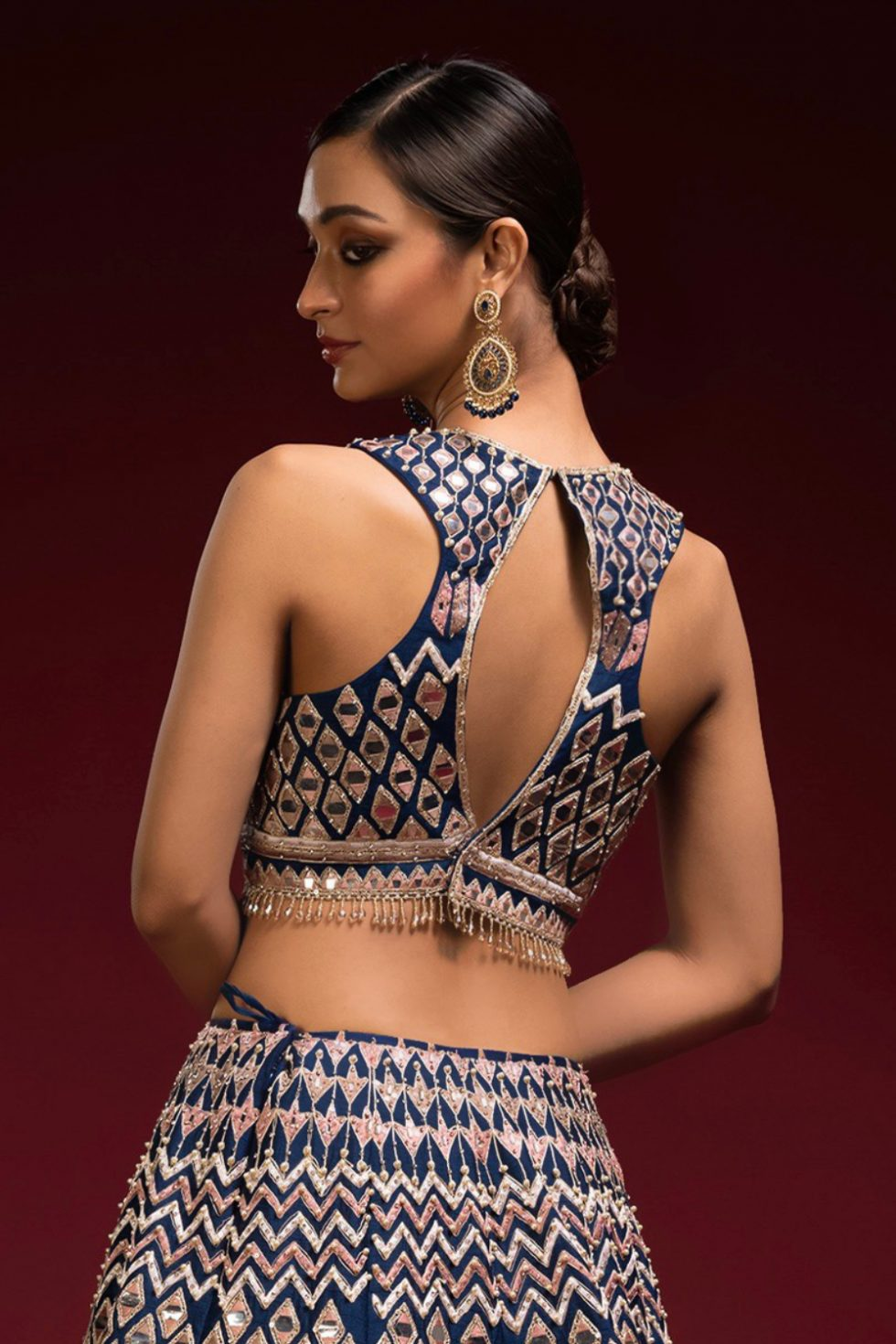 Deep blue blouse with multi coloured thread work, keyhole back and tassels.